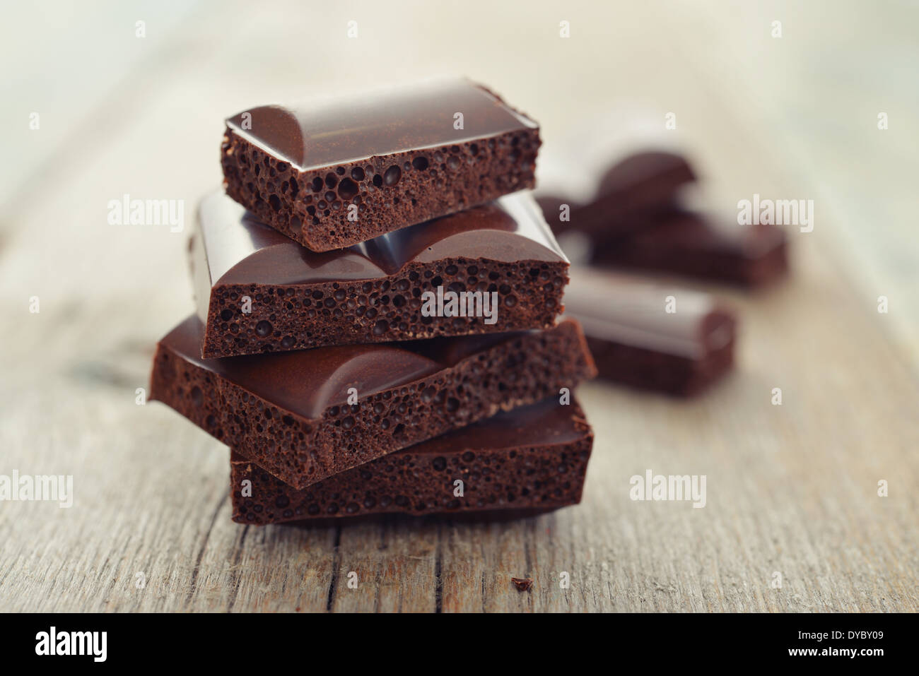 Porous chocolate in stack on a wooden background closeup Stock Photo