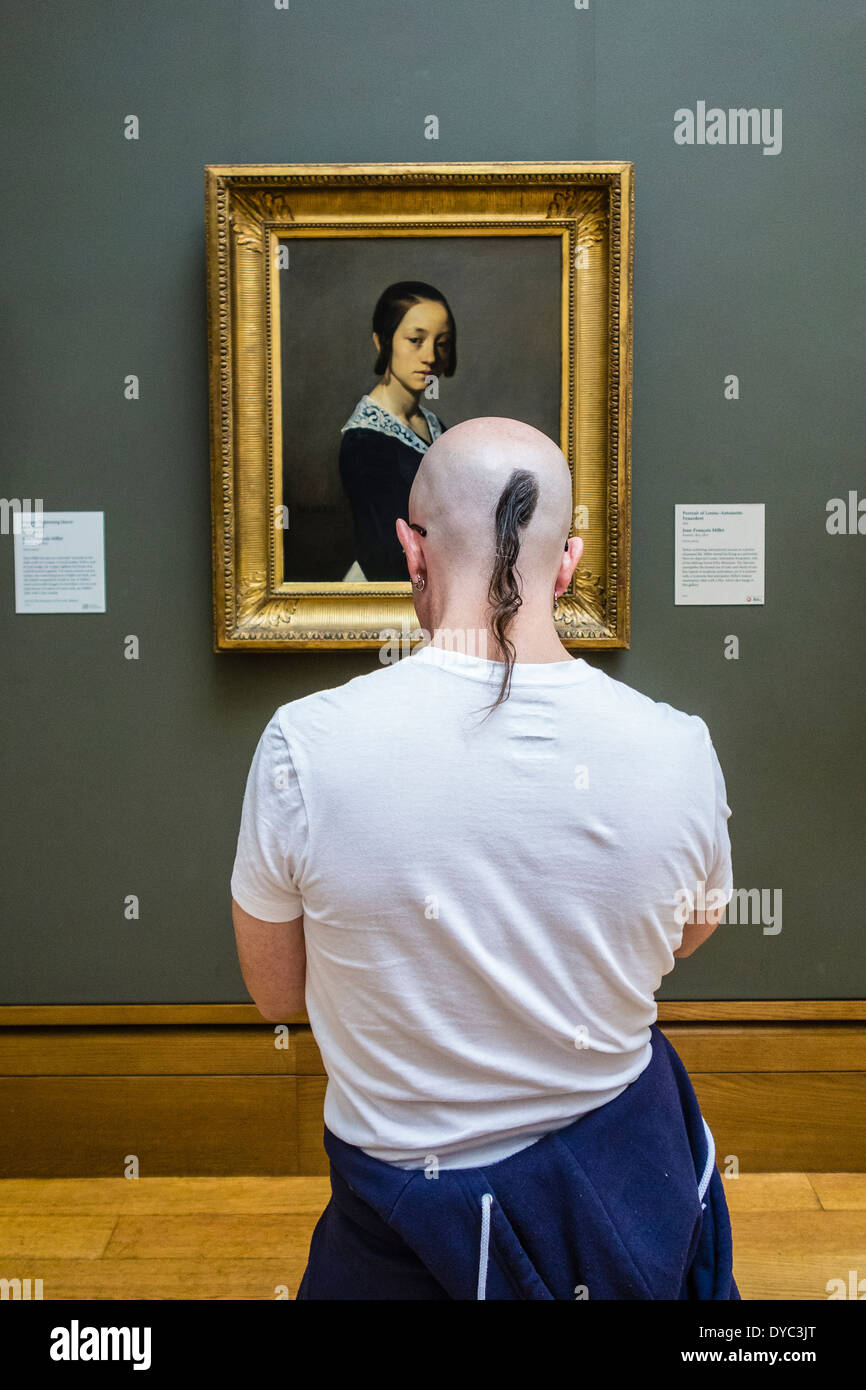 A young adult male with a shaved head and a pony tail of hair views a painting on the wall of a museum. - Stock Image