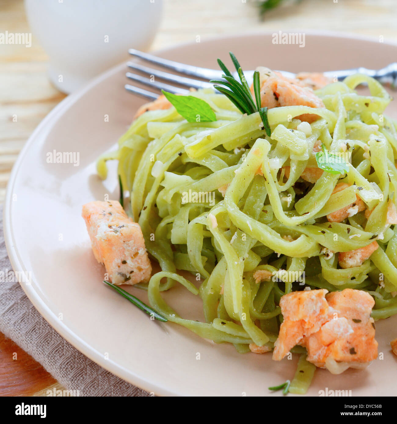appetizing pasta with spinach salmon, food closeup - Stock Image