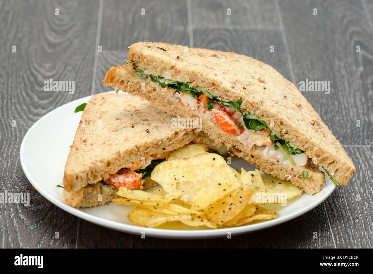 A crayfish and prawn sandwich with fresh rocket (aragula) and potato crisps on a white plate - studio shot - Stock Image