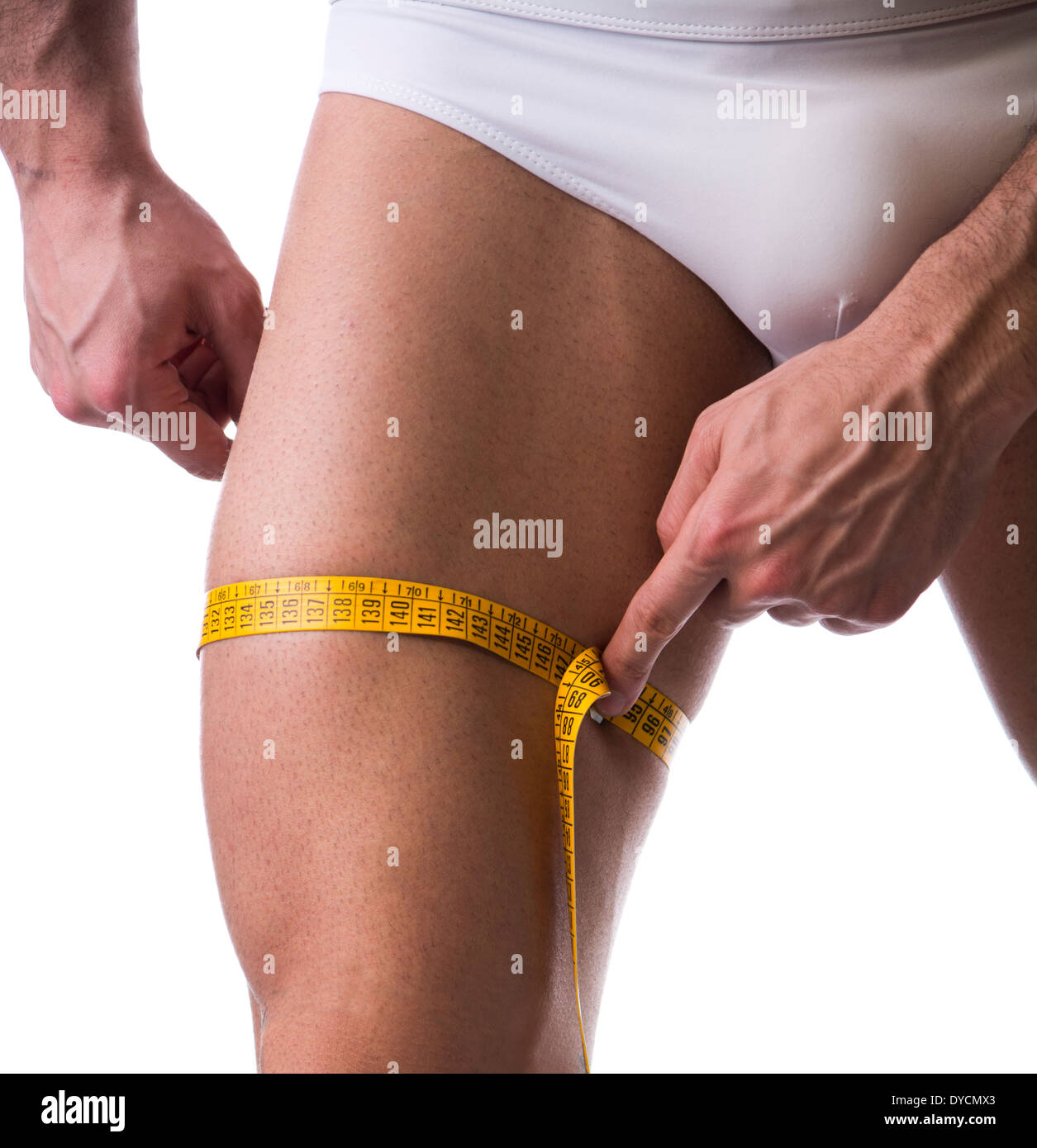 Muscular young man measuring thigh with tape measure, close-up of leg on white background - Stock Image