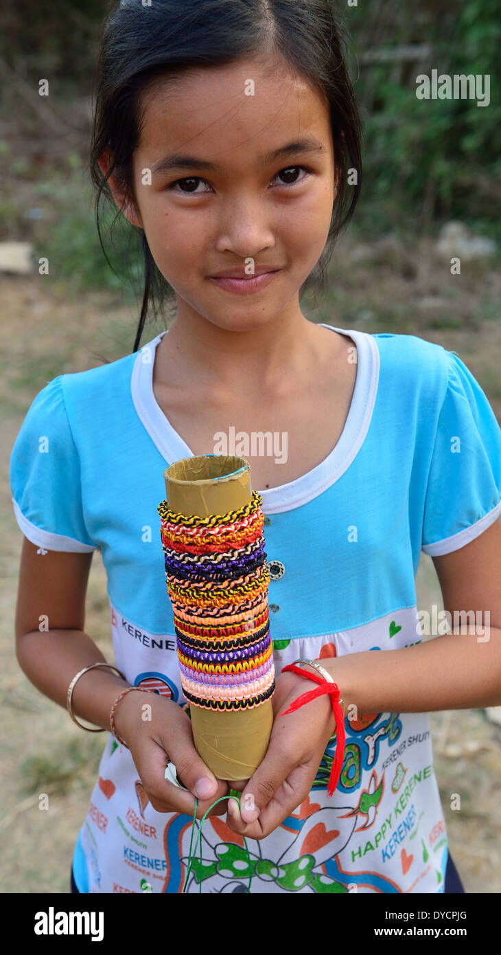 Young Cambodian girl offers her grass bracelets and rings.jewelry for sale to  Bamboo Train passengers at O Sra Lav village - Stock Image