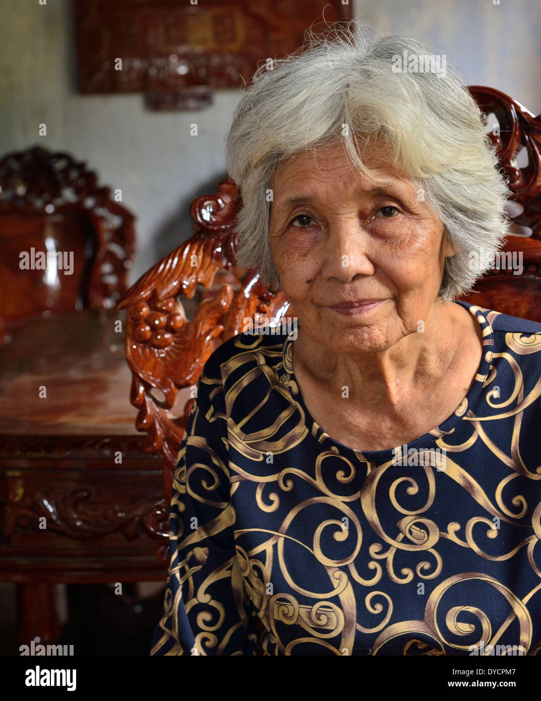 Diminutive 67-year-old Yi Layieng posed Inside the first room of the plaster-walled pét house in Wat Kor, Battambang - Stock Image