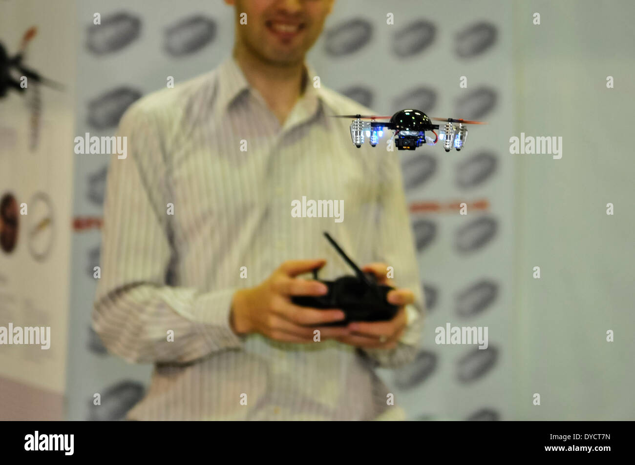 A man flies a miniature quad-copter drone - Stock Image