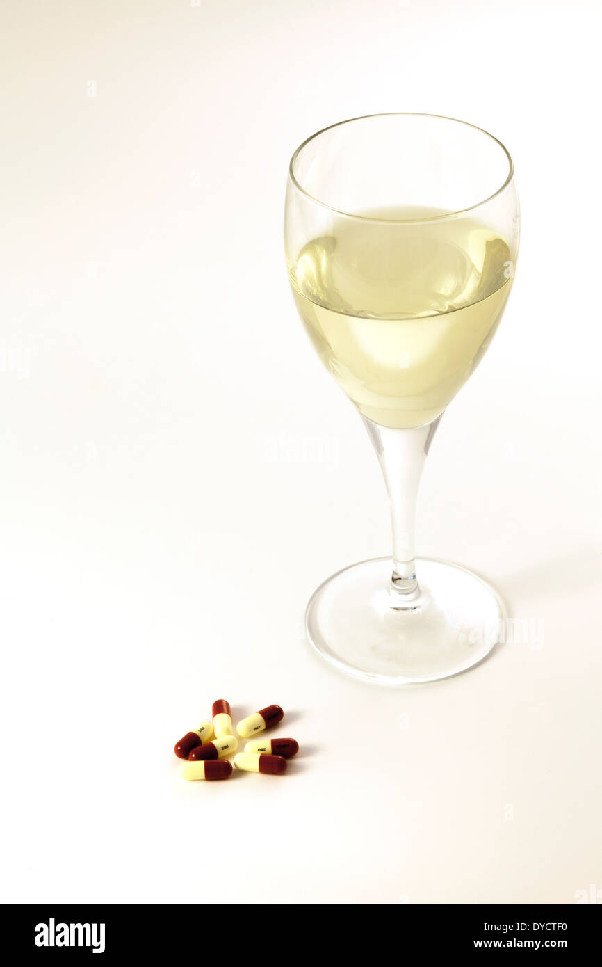 Medications and alcohol interaction - white wine and medicine capsules, UK - Stock Image