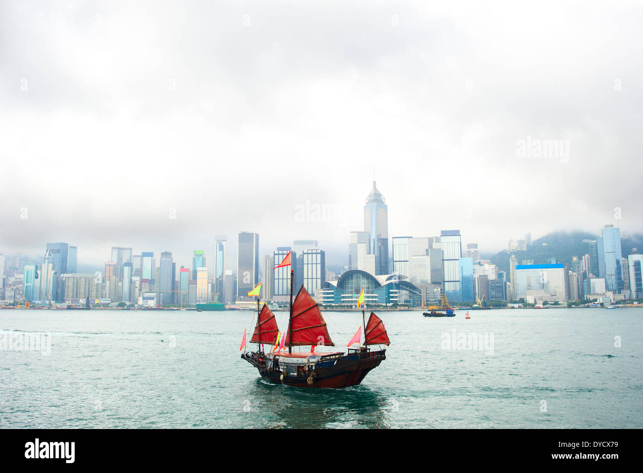 View on Hong Kong downtown from the sea with traditional chinese sailboat - Stock Image