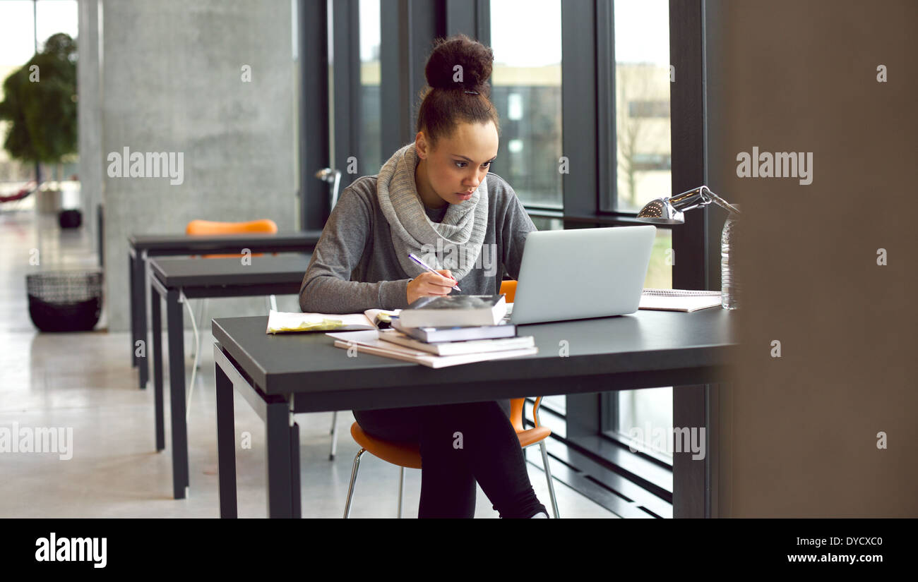 Young afro american woman sitting at table with books and laptop for finding information. Young student taking notes from laptop - Stock Image