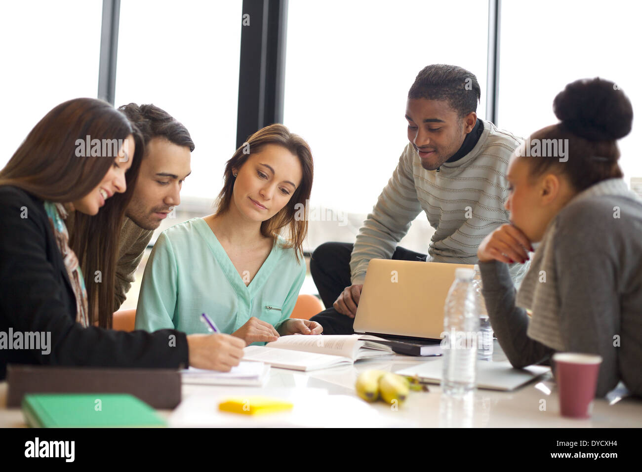 Diverse group of young students working together on school assignments. Multiethnic people studying together at a table. - Stock Image