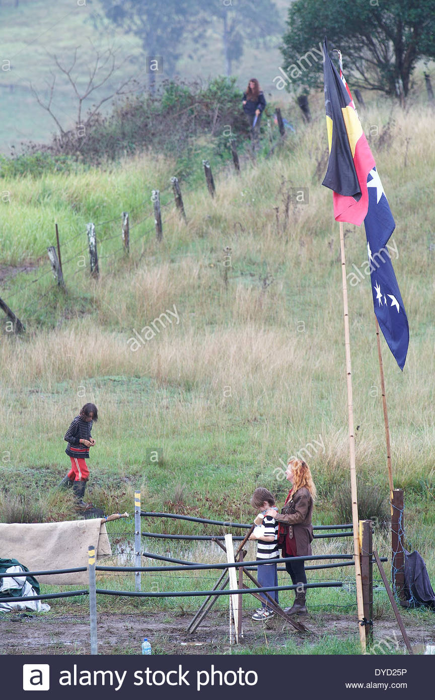 A Caucasian woman stands behind her son, in front of Australian and Indigenous flags - a gesture of solidarity - during the Bentley Blockade, 2014. - Stock Image