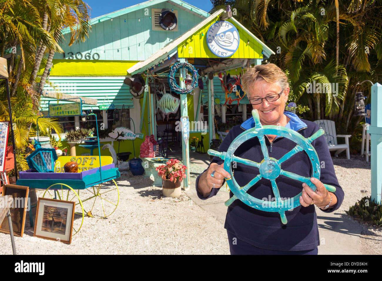 Port Charlotte Florida Harbor Placida Art Market sign Hatch Gallery shopping exterior colorful senior woman boat steering wheel - Stock Image