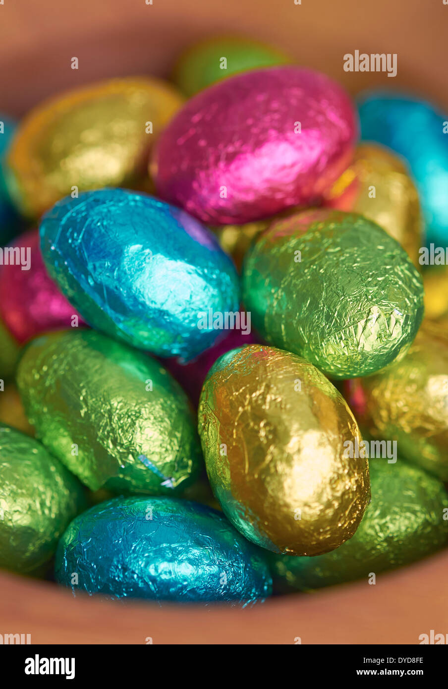 Colouful foil wrapped easter eggs in a bowl. - Stock Image