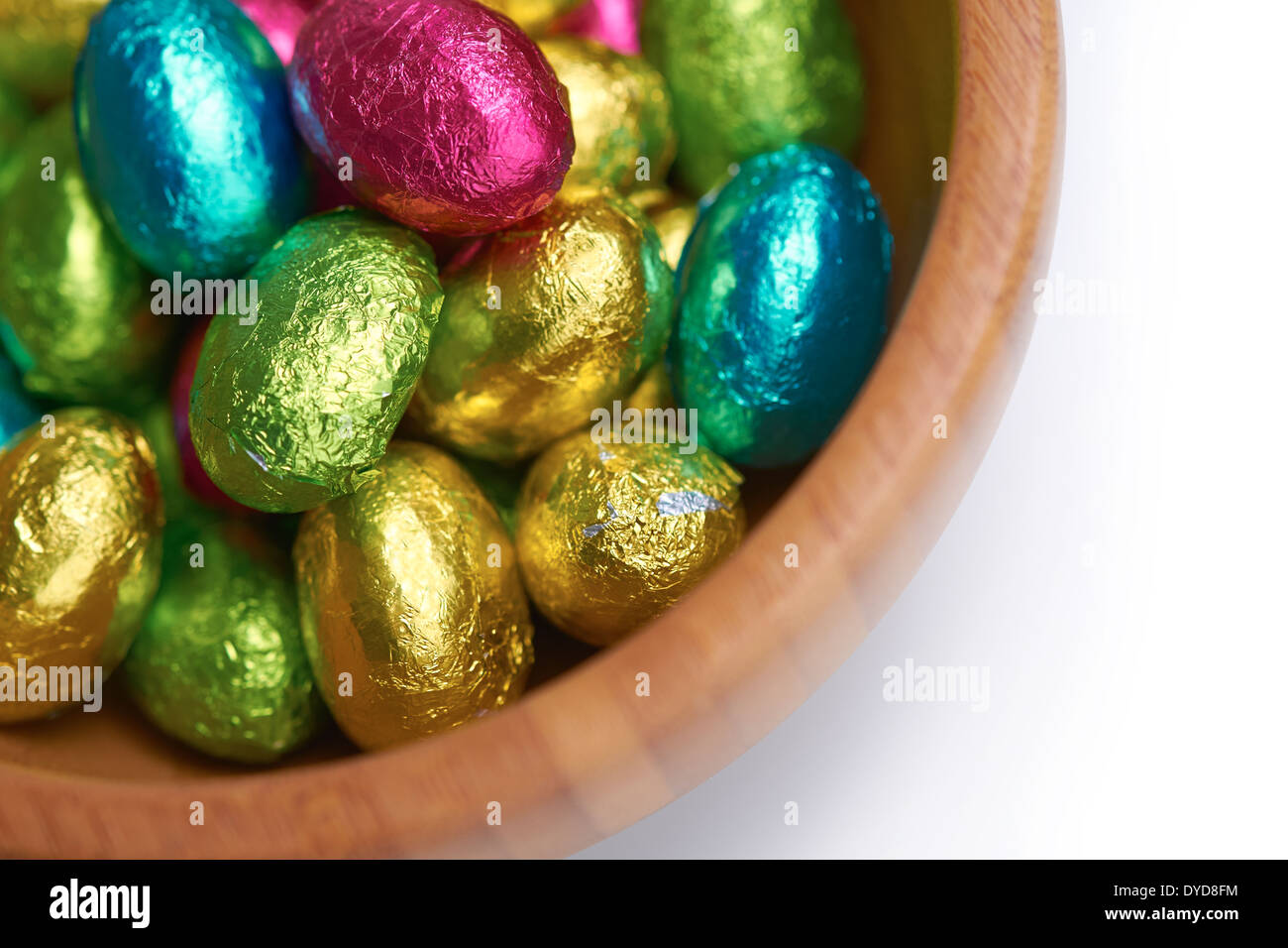 Colouful foil wrapped easter eggs in a bowl on a white isolated background. - Stock Image