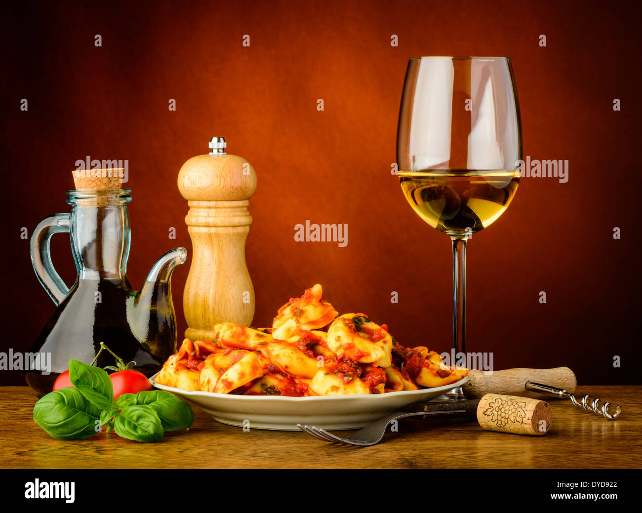 still life with traditional tortellini pasta meal and glass of white wine - Stock Image