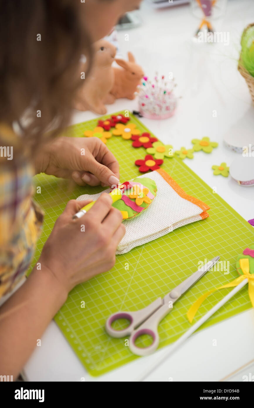 Closeup on young woman making easter decorative egg. rear view Stock Photo