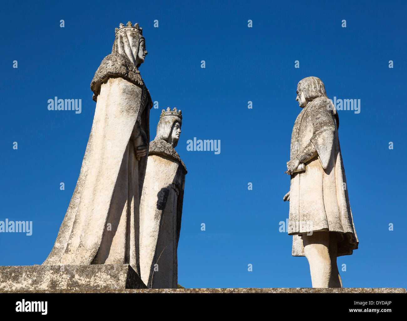 Stone statues of the monarchs Fernando and Isabel on the left and Columbus, in the garden of the Alcázar de los Reyes - Stock Image