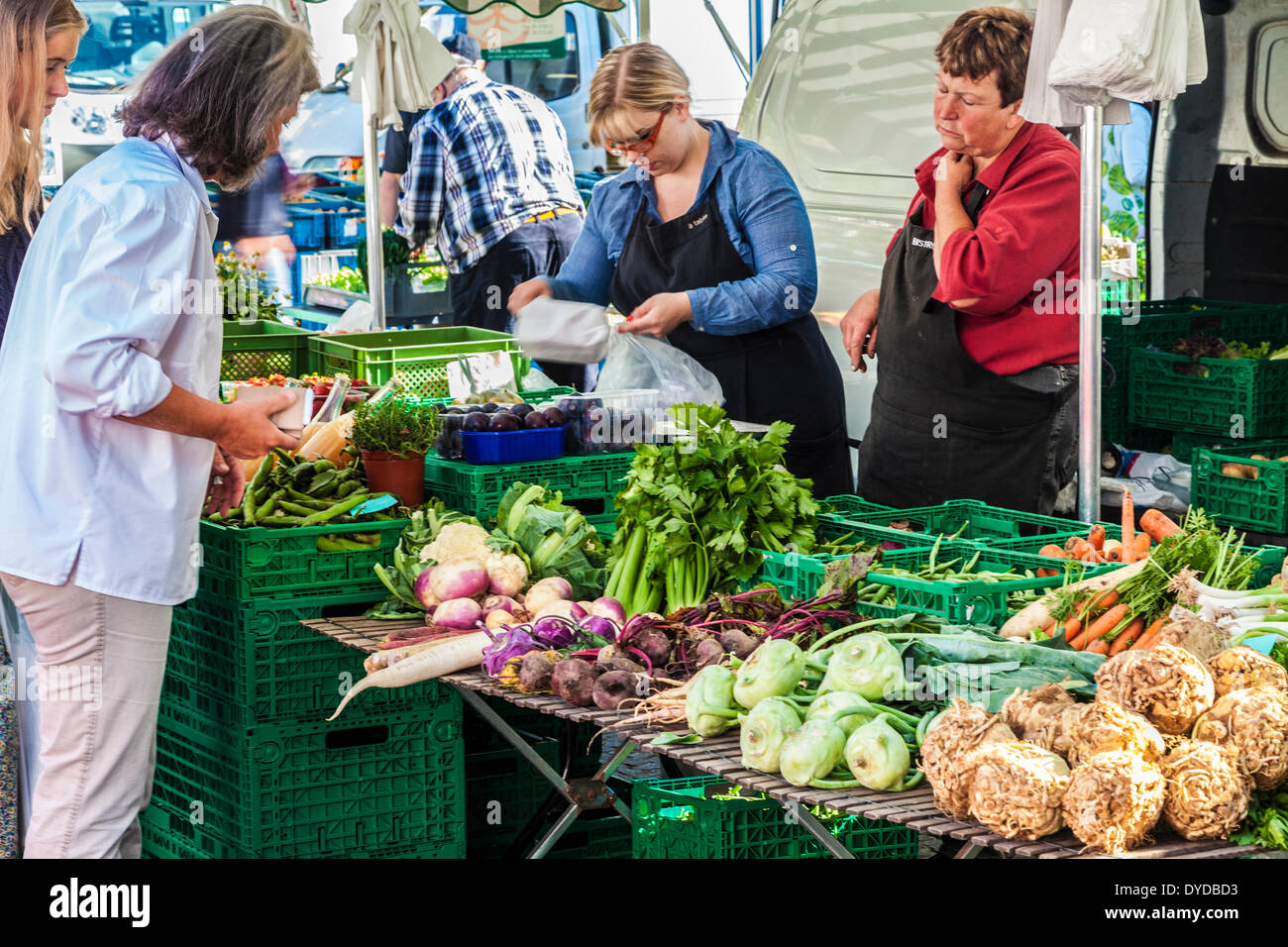Buying and selling fresh produce from a vegetable stall at the market in the Place Guillaume II in Luxembourg. - Stock Image