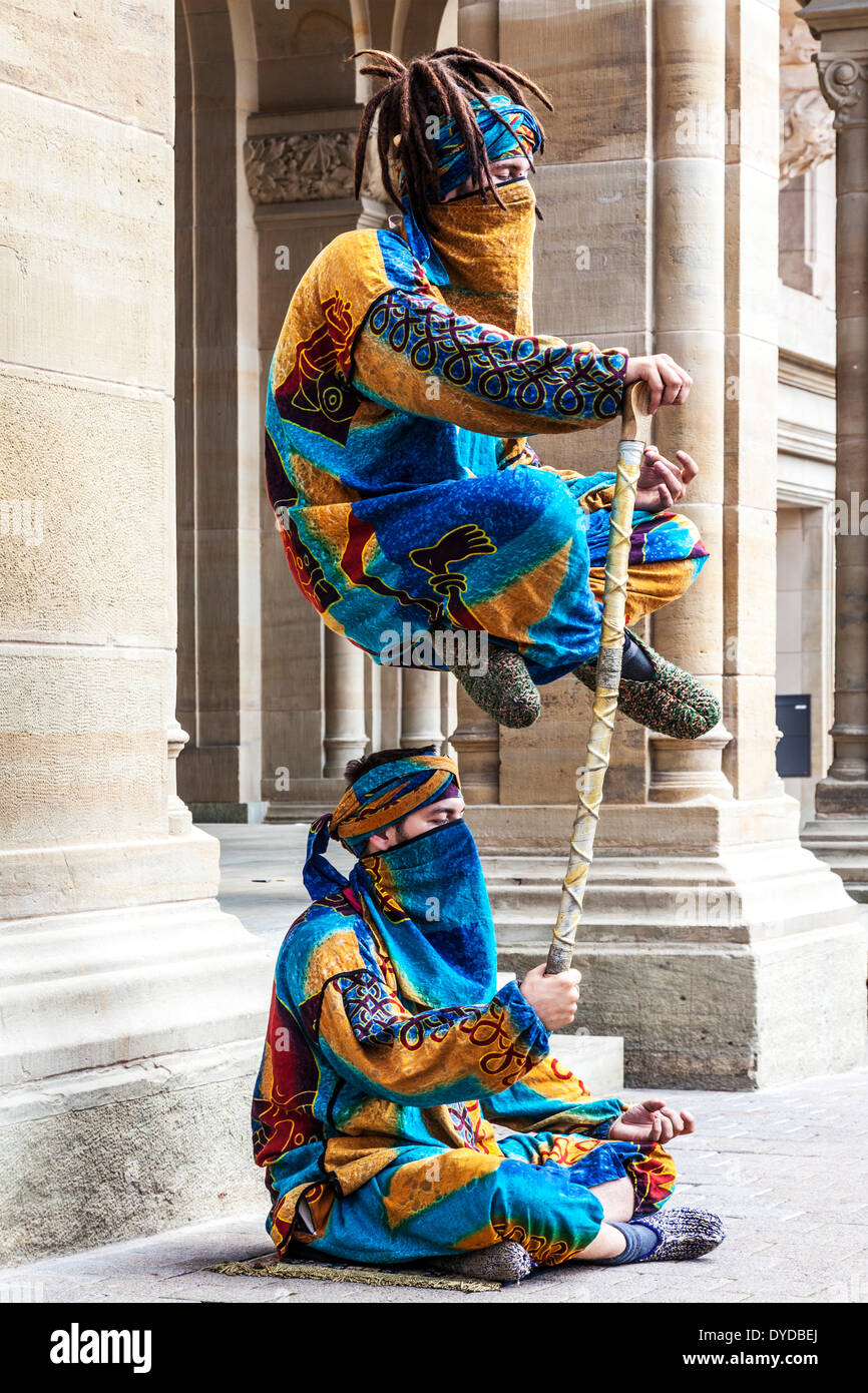 Two street entertainers performing a levitation trick in the Place d'Armes in Luxembourg City. - Stock Image