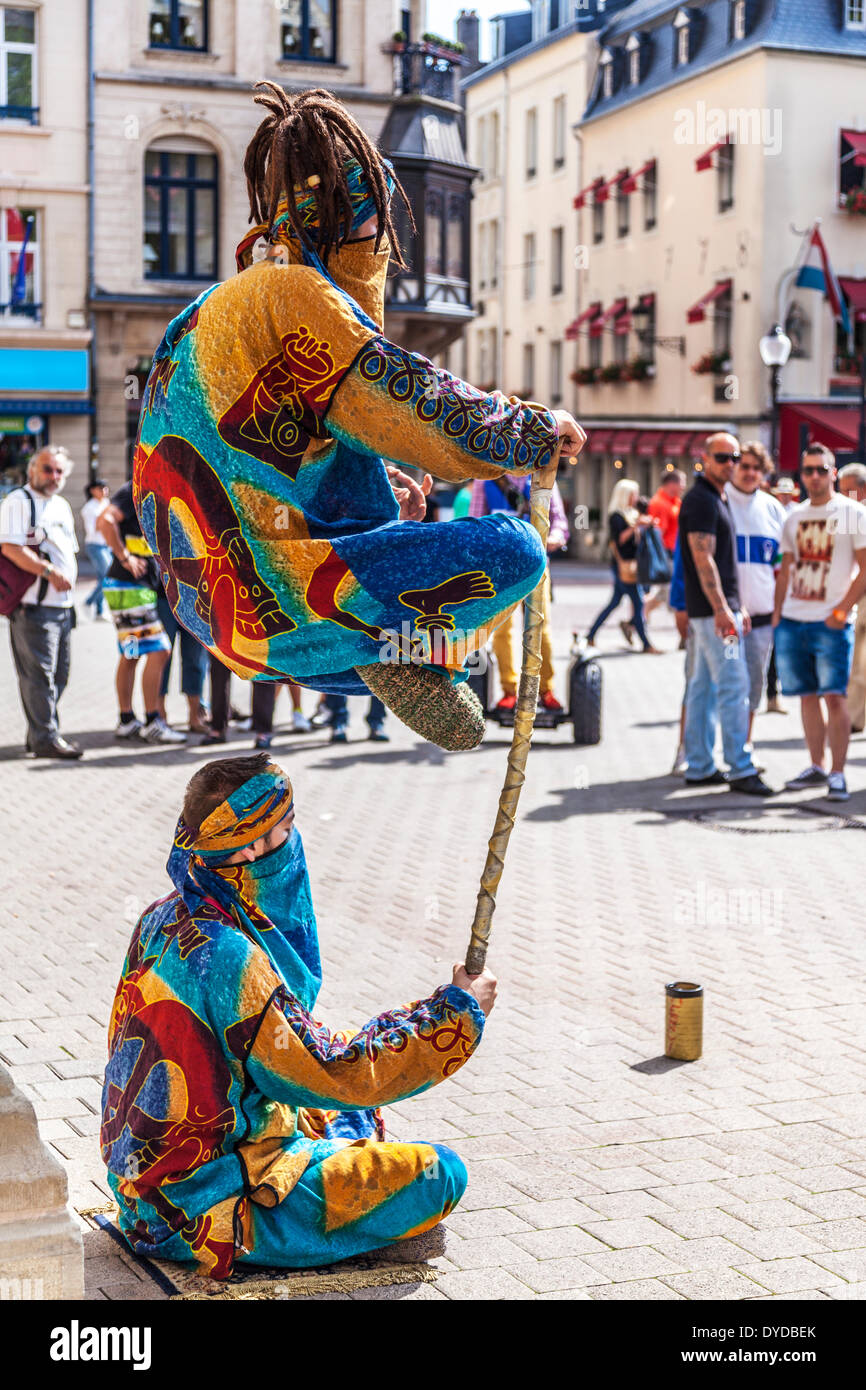 Tourists watching two street entertainers performing a levitation trick in the Place d'Armes in Luxembourg City. - Stock Image