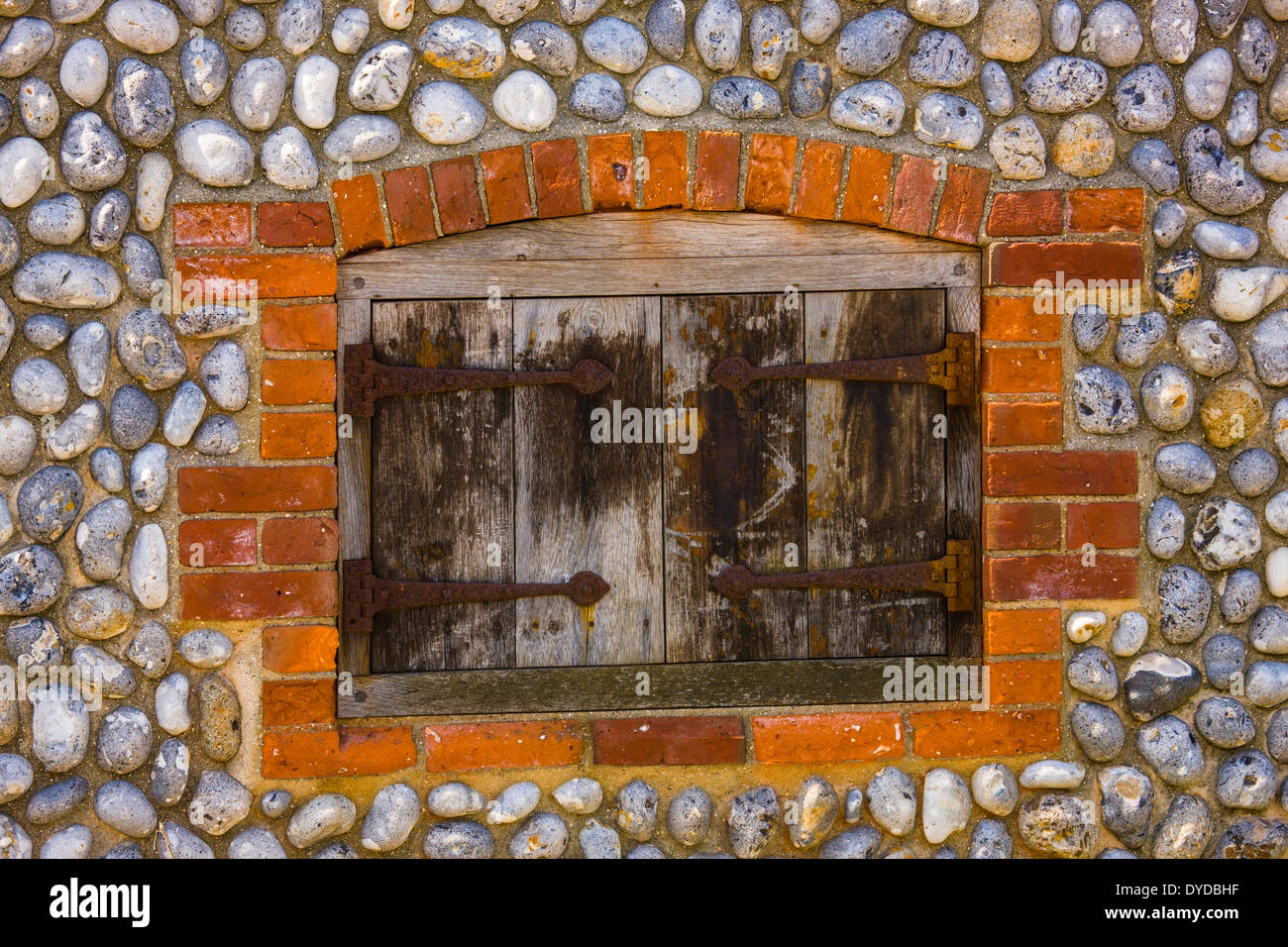 Shuttered window in brick and flint wall. - Stock Image