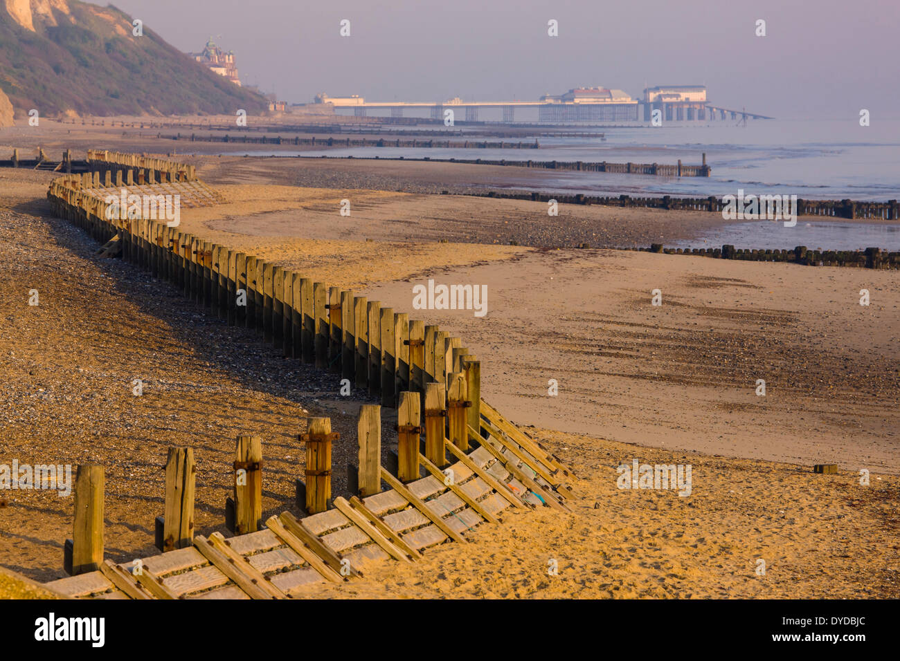 Breakwaters at Overstrand beach with Cromer pier in the distance. - Stock Image