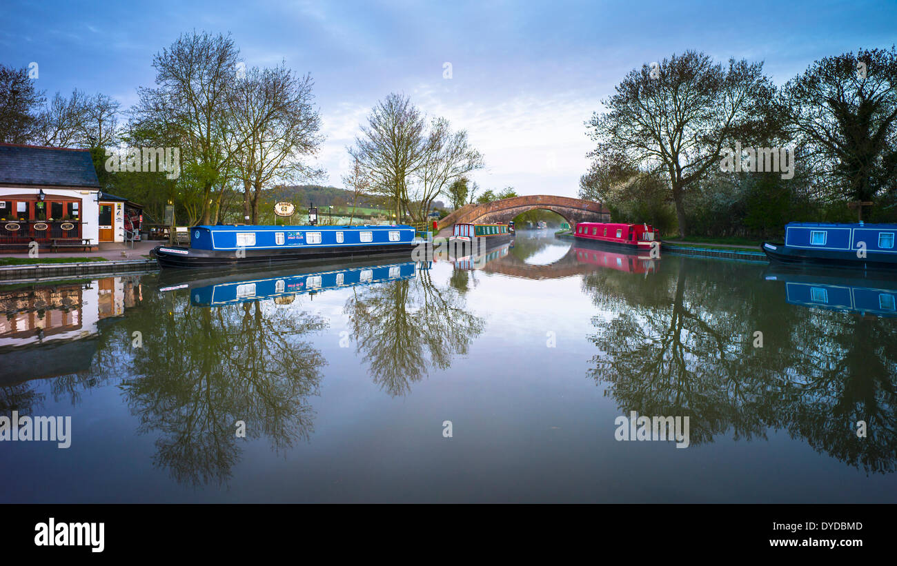 Canal basin on the Grand Union canal showing one of the pubs and a hump backed bridge. - Stock Image