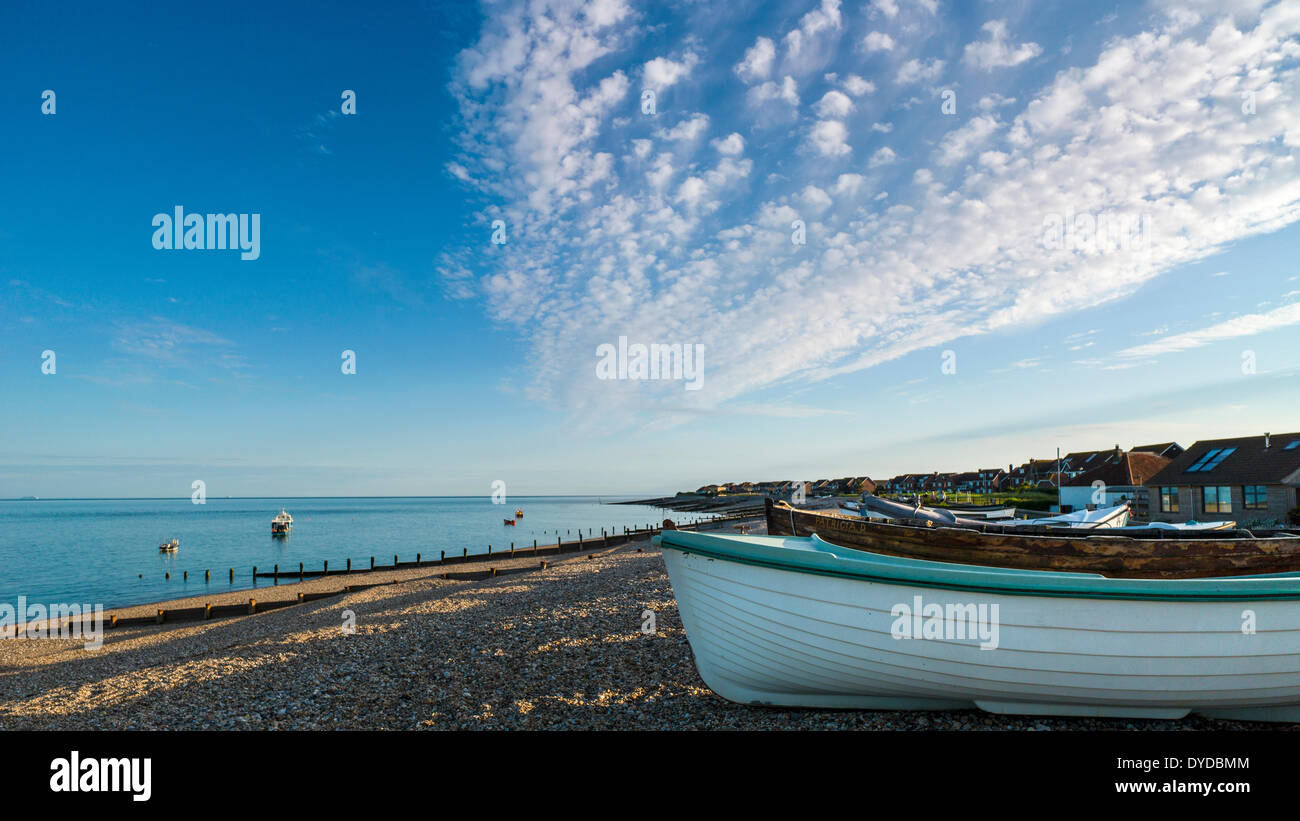View along Selsey beach near sunset with small boats drawn up on the shingle. - Stock Image