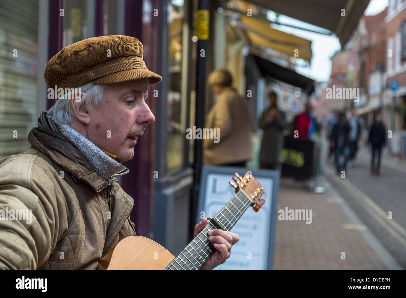 Busker playing a guitar in a busy street. - Stock Image