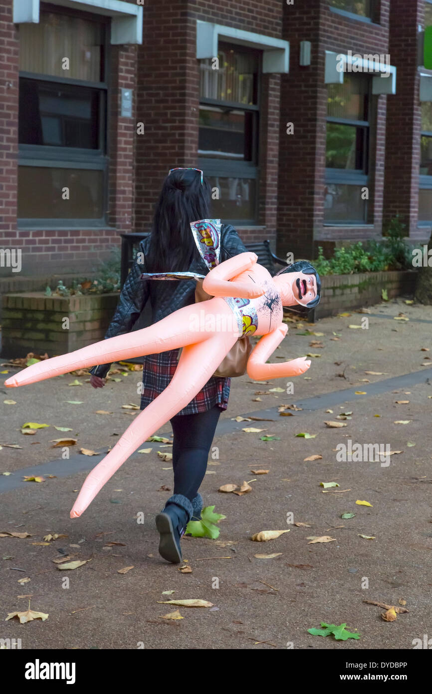 Girl carrying a blow up doll through a city street. - Stock Image