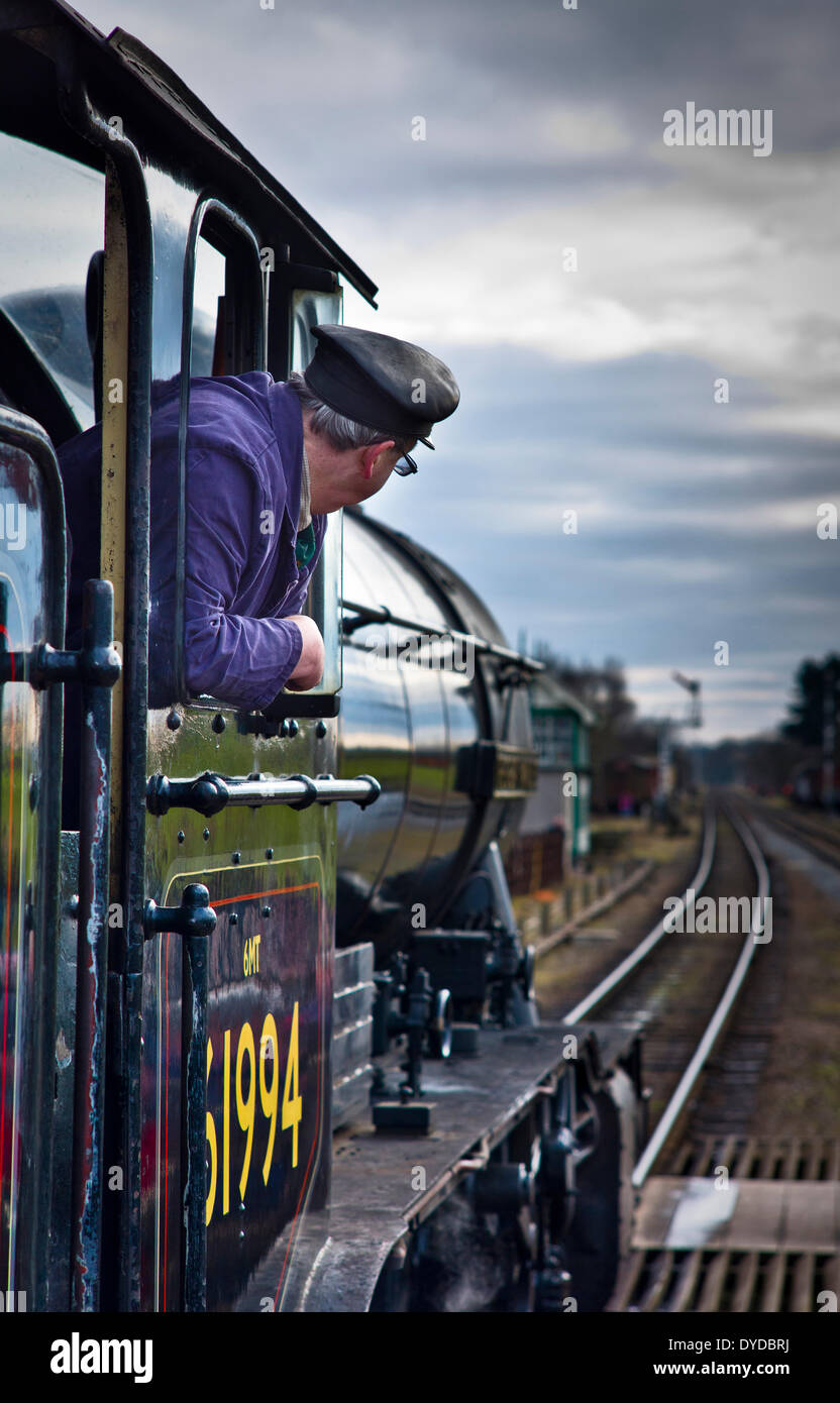 The engine driver looks out of the cab of a steam engine on the Great Central Railway at Quorn Station. - Stock Image