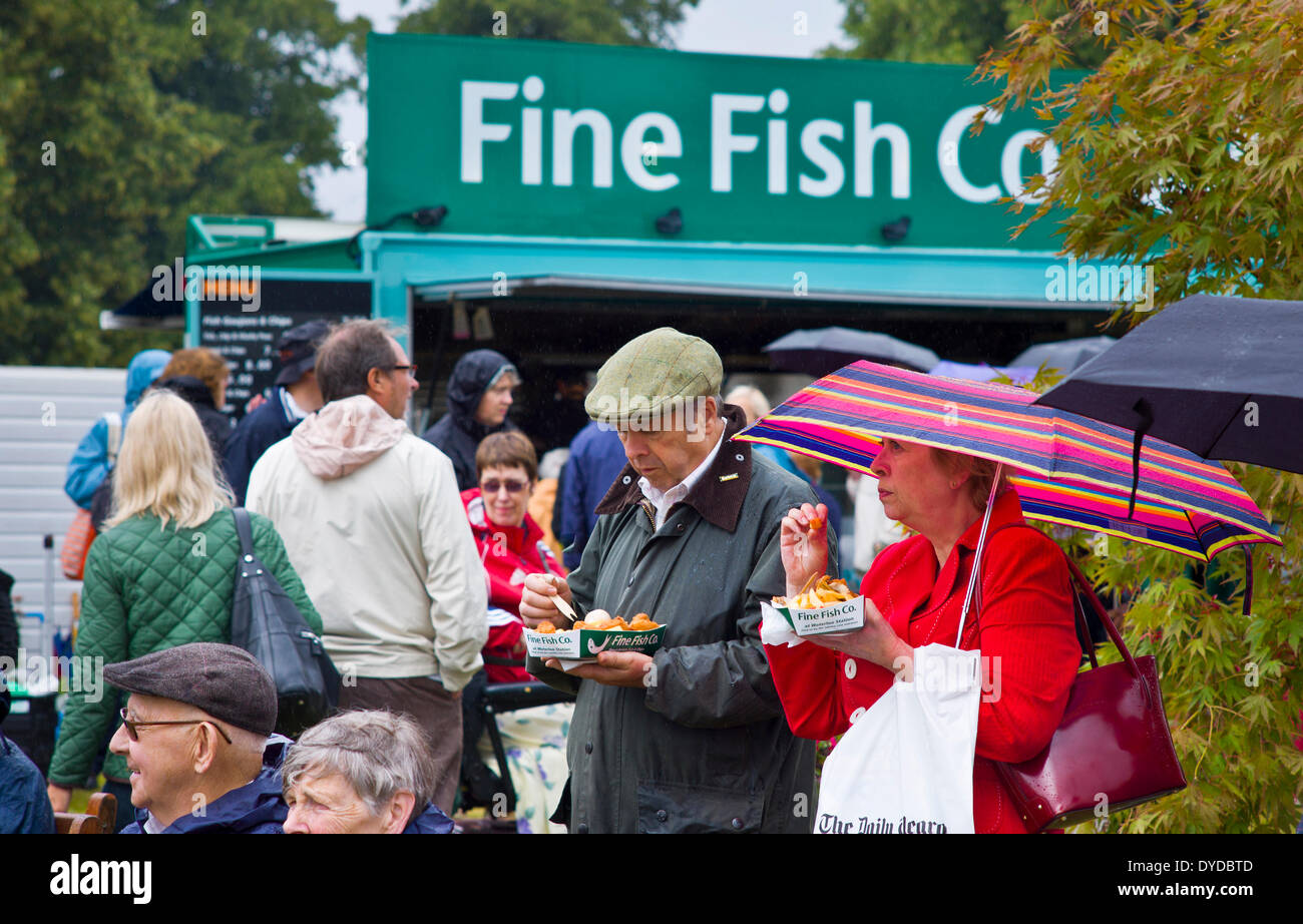 Eating fish and chips outside the catering trailer of the Fine Fish Co. - Stock Image