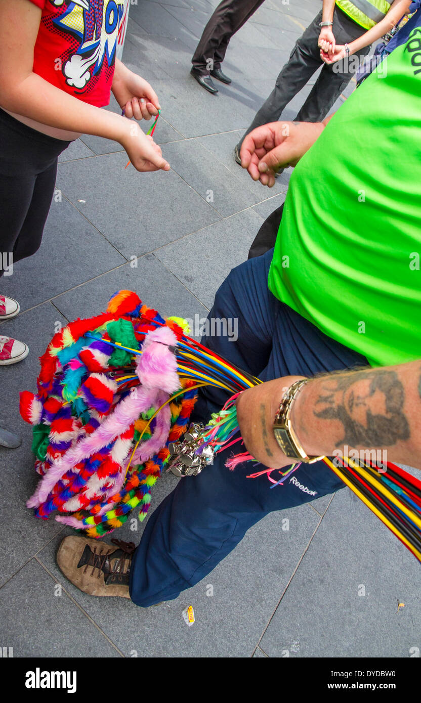 Street vendor selling whistles and tails to a young girl. - Stock Image