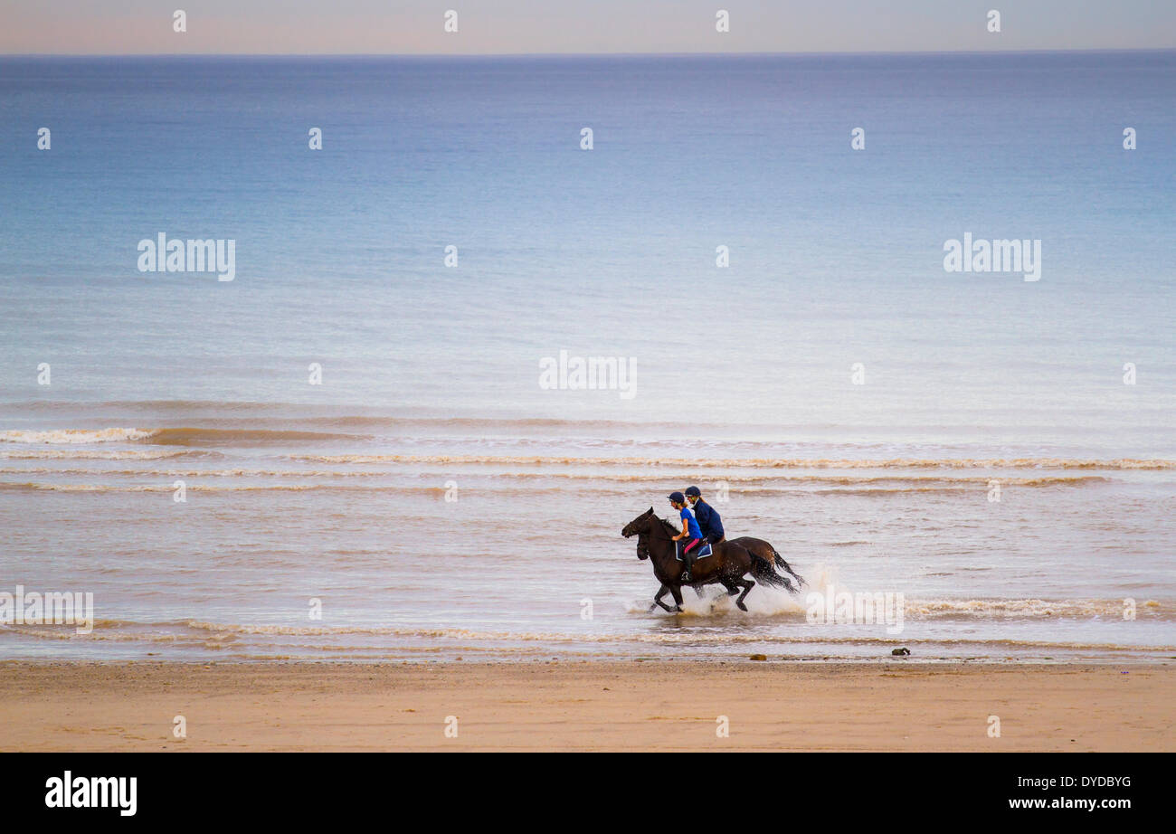 Riders galloping along a beach. - Stock Image