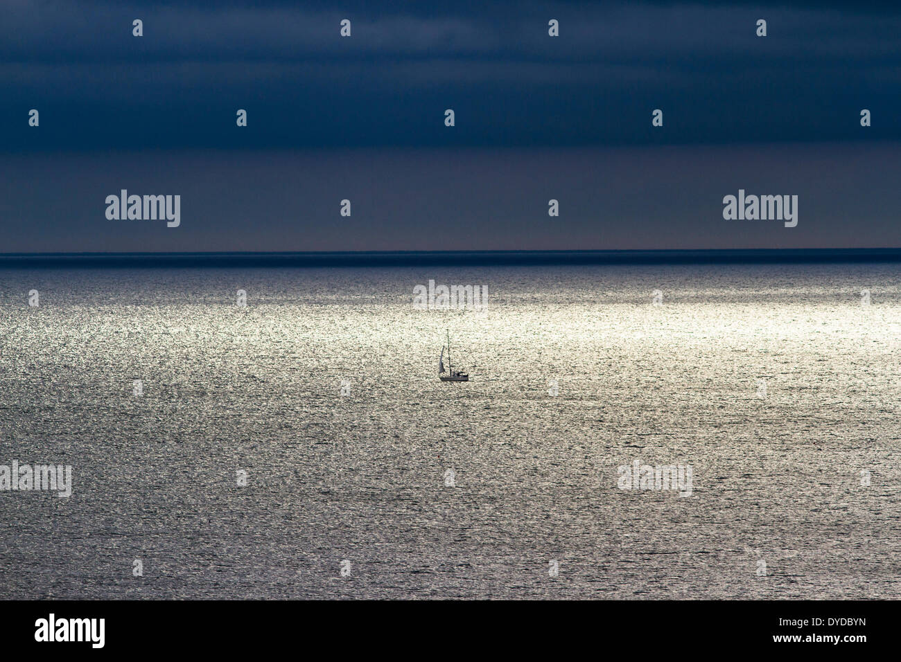 A small yacht under sail far out at sea. - Stock Image