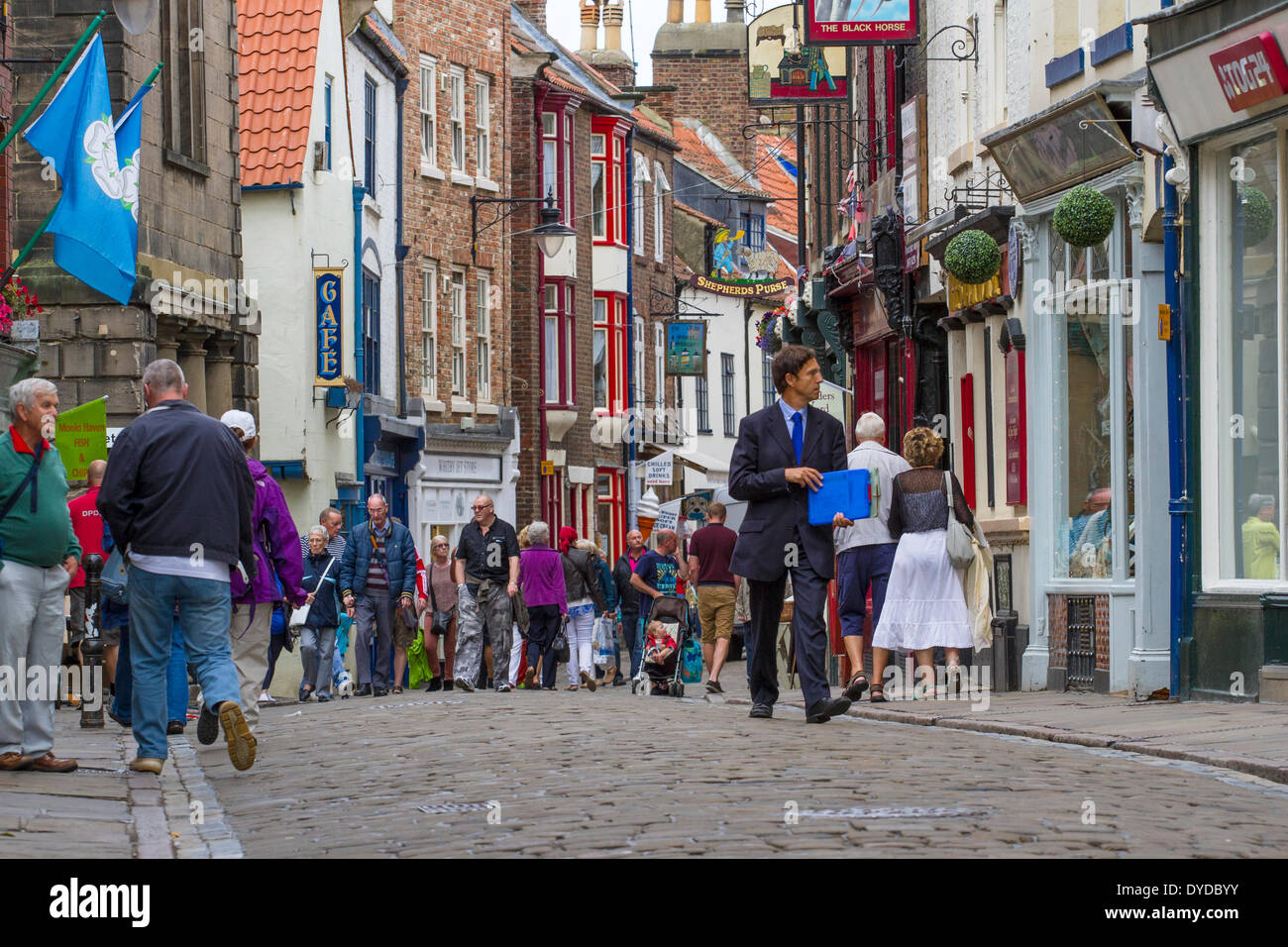 Crowds of holidaymakers in Whitbys narrow streets. - Stock Image