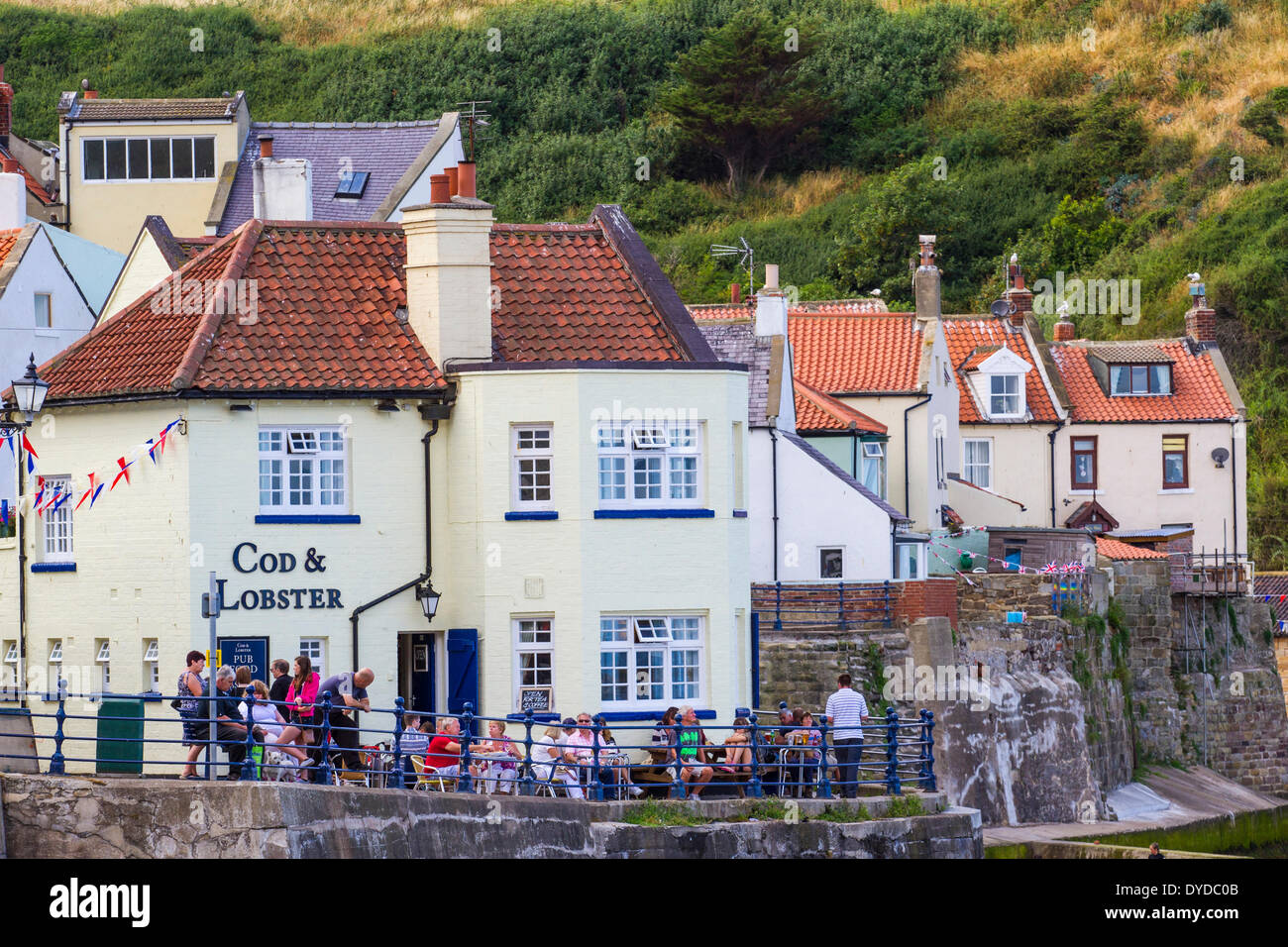 Holidaymakers enjoying a drink at a seaside pub. - Stock Image