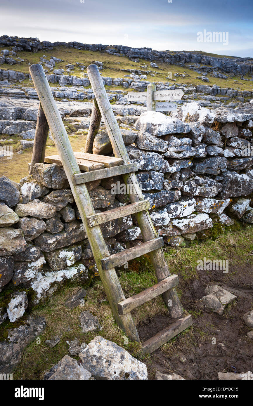 A wooden stile over a stone wall in the Yorkshire dales adjacent to a sign for the Pennine way at Malham Cove. - Stock Image