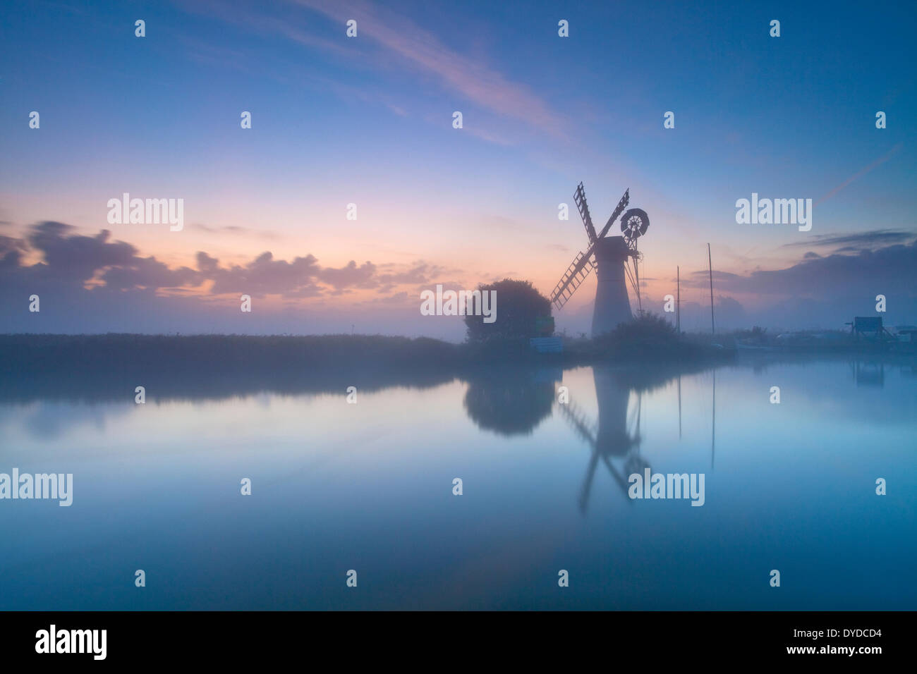 Thurne Mill at sunrise on a misty morning on the Norfolk Broads. - Stock Image