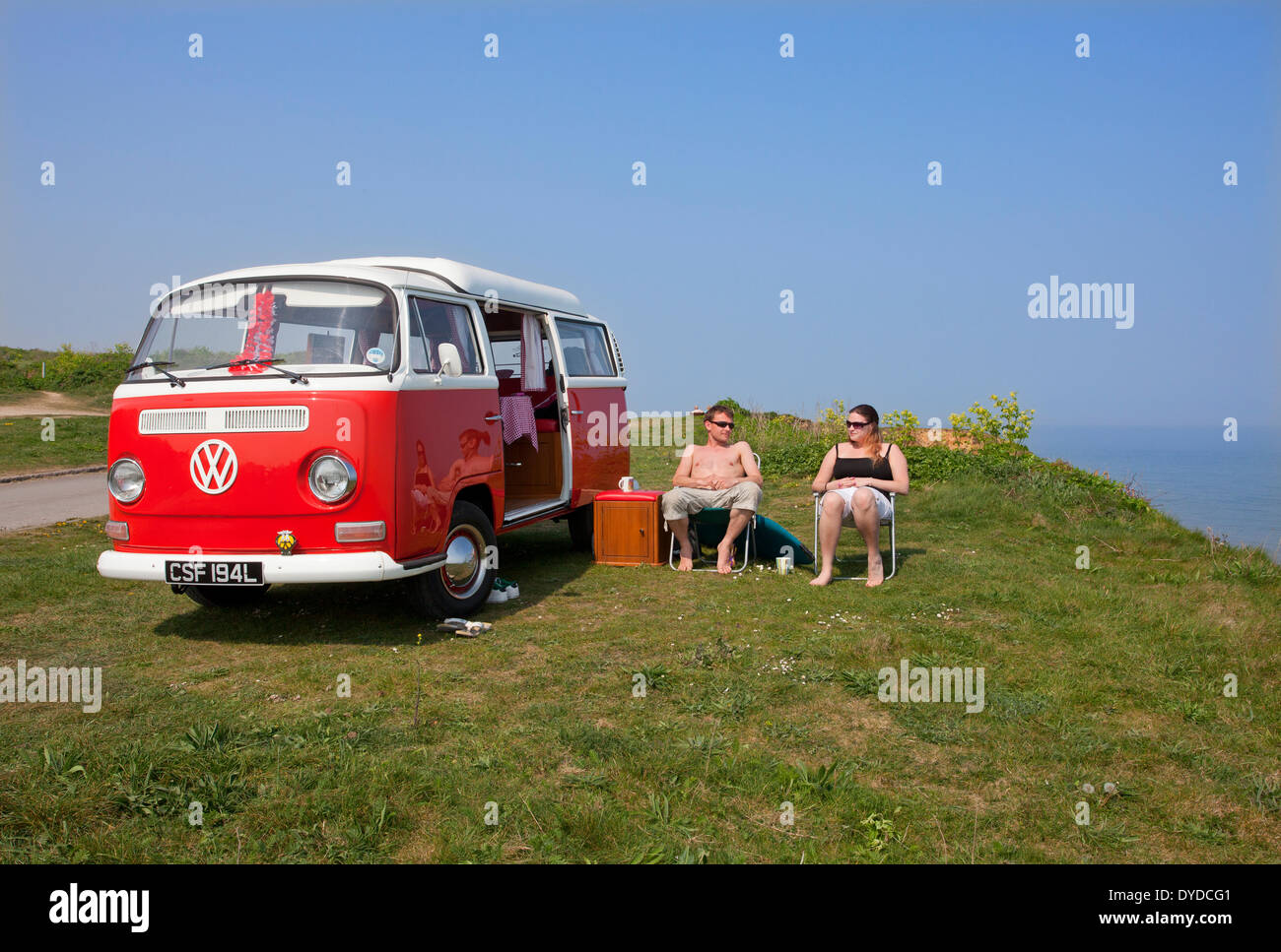 A young couple camping in a VW campervan on the clifftops over Mundesley on the Norfolk coast. - Stock Image