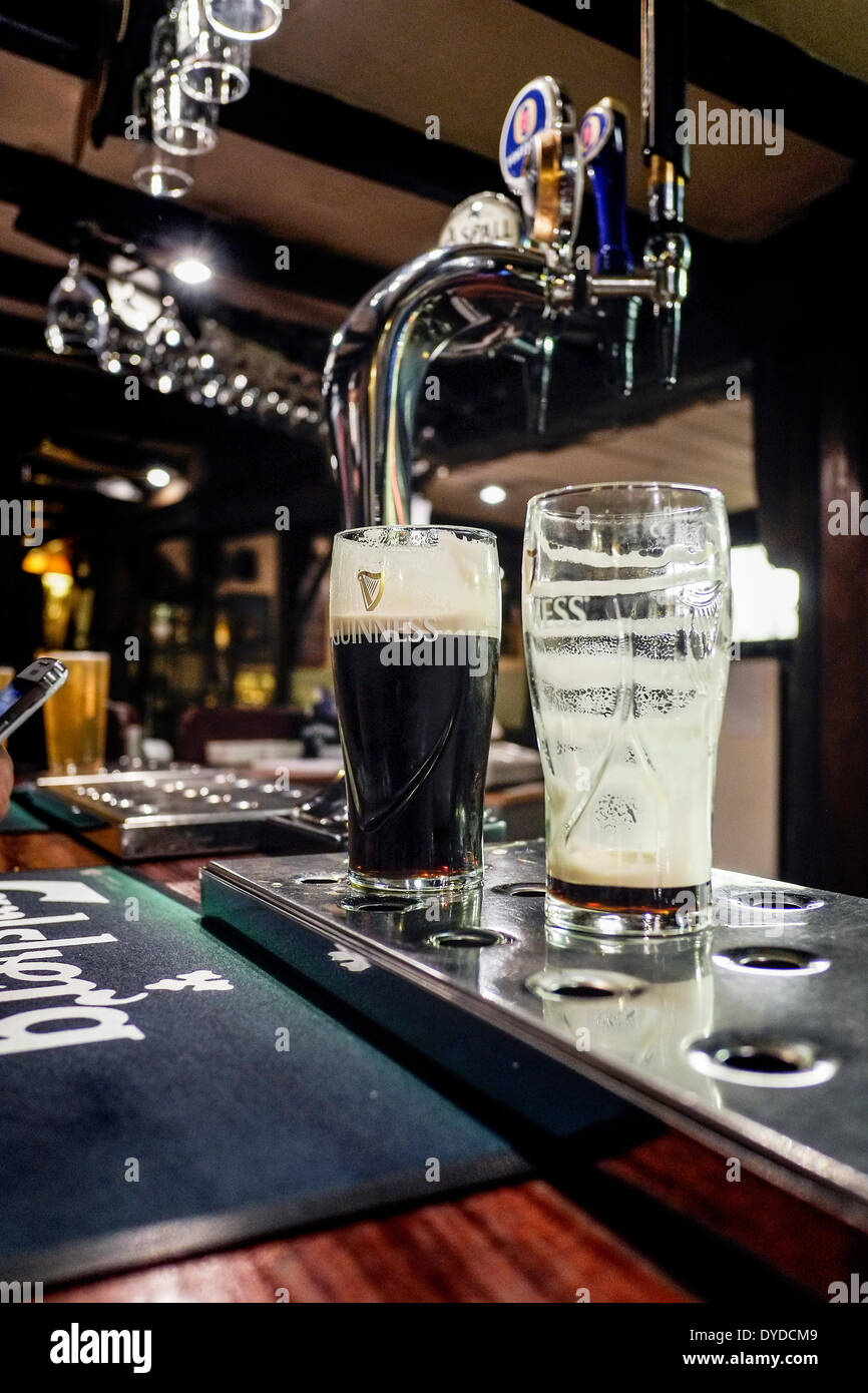 Pint glasses of Guinness on the bar of a pub. - Stock Image