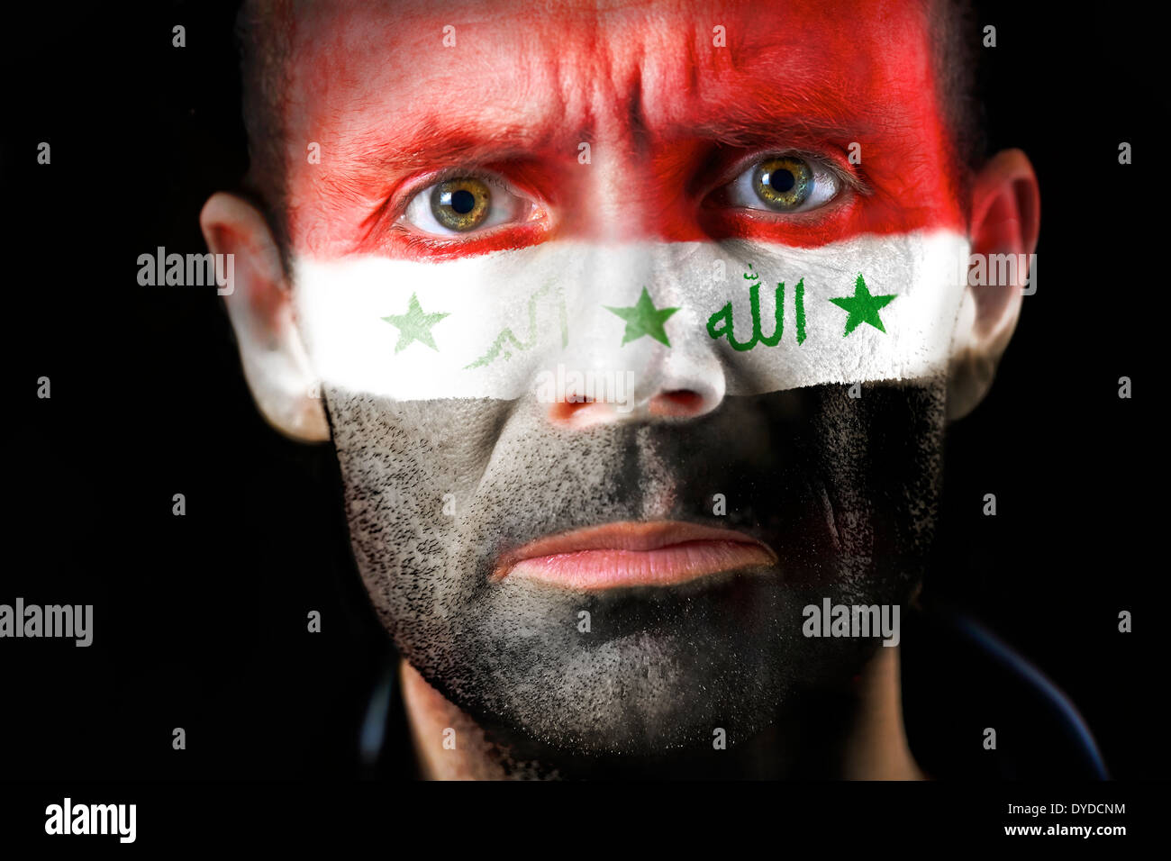 An intense stare from a man with their face painted with the Iraq flag. - Stock Image