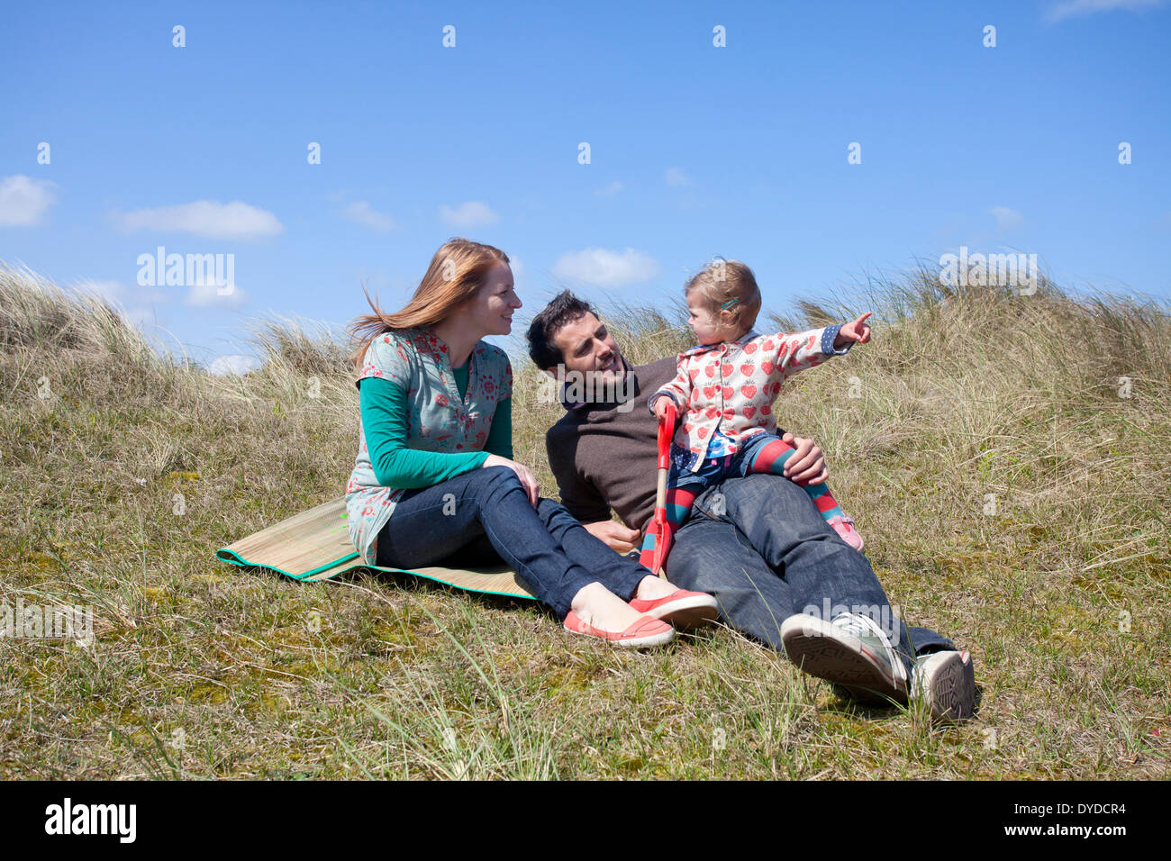 A young family having fun on the sand dunes at Horsey Beach on the Norfolk coast. - Stock Image