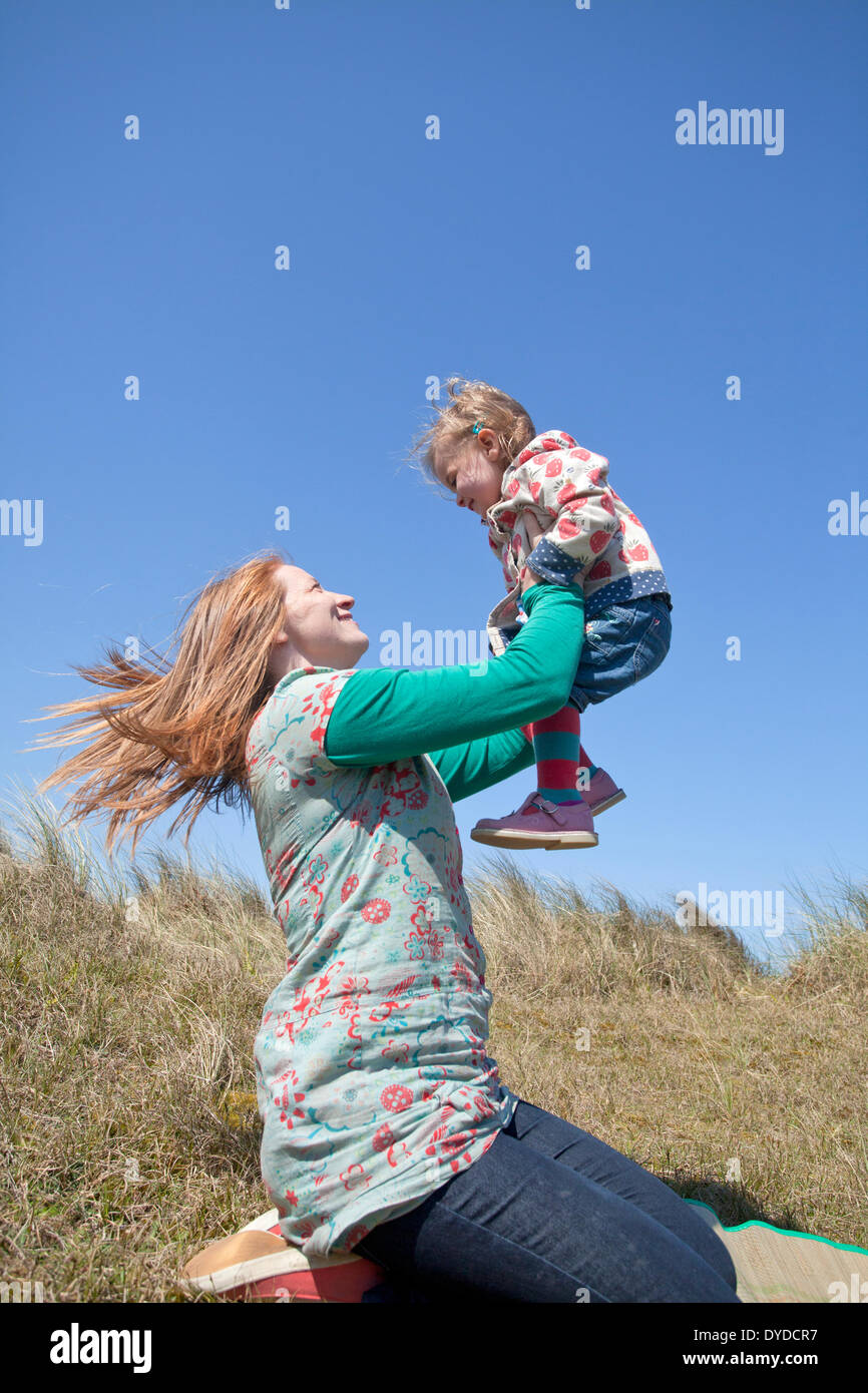 A mother playing with her daughter on Horsey sand dunes on the Norfolk coast. - Stock Image