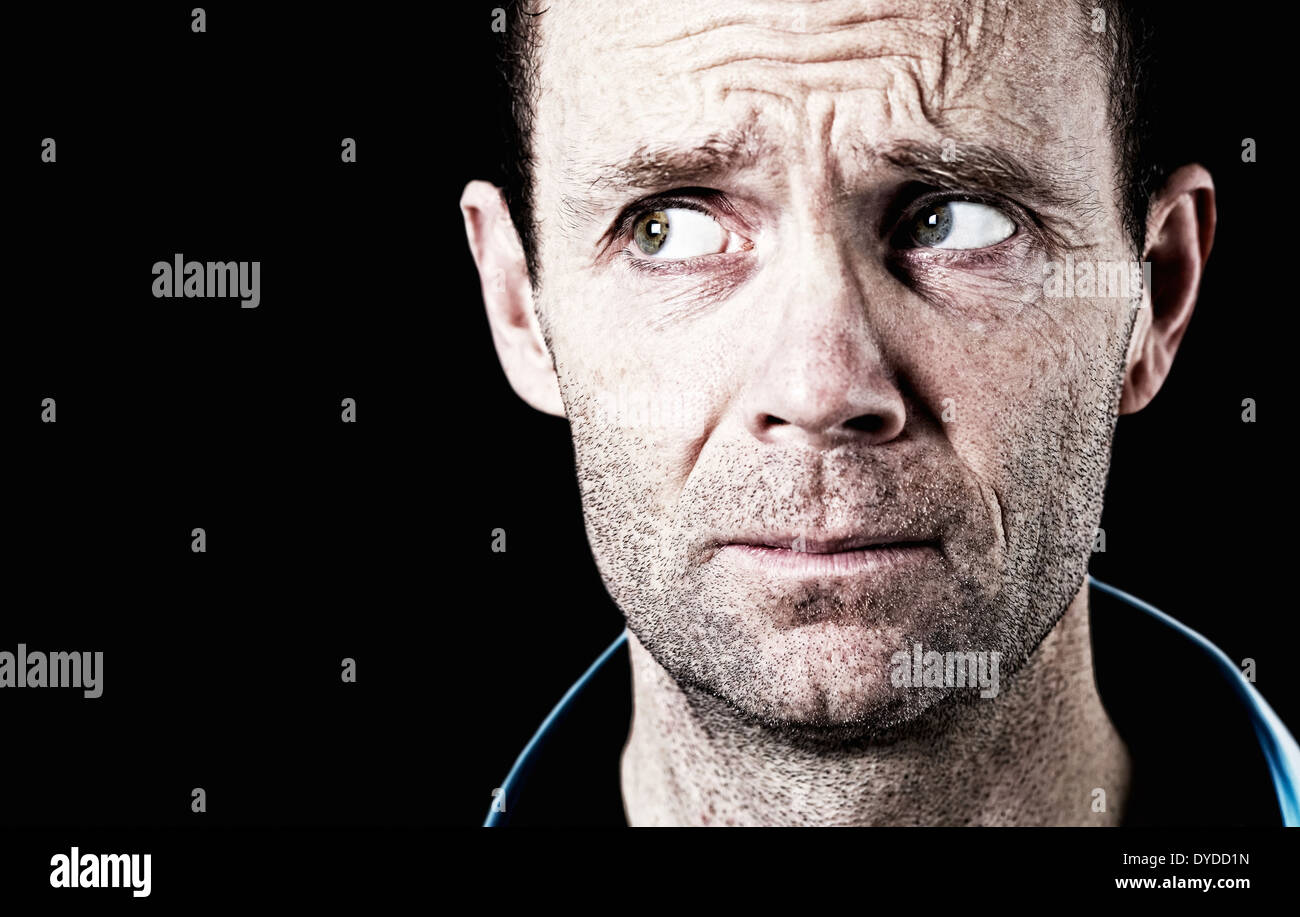 A portrait of a man taking a sidewards glance. - Stock Image