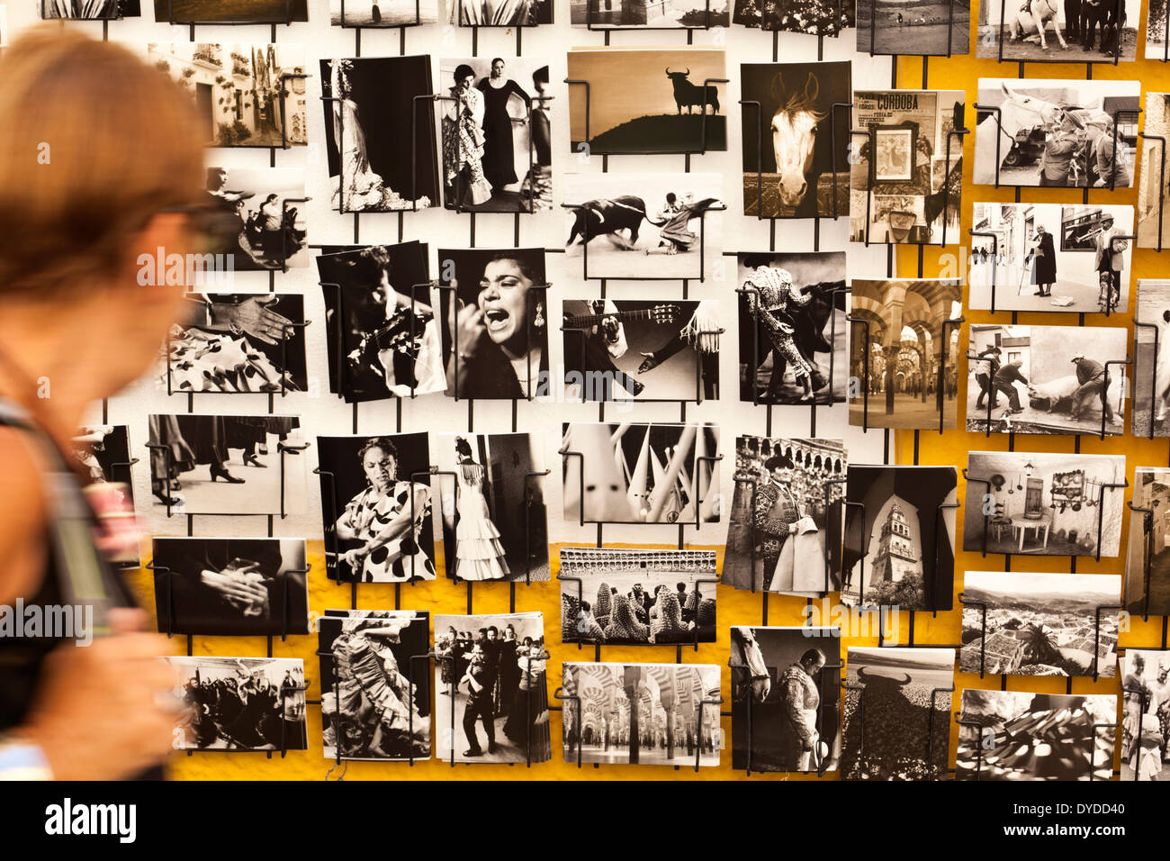 A tourist views a rack of black and white postcards of old Andalucia. - Stock Image