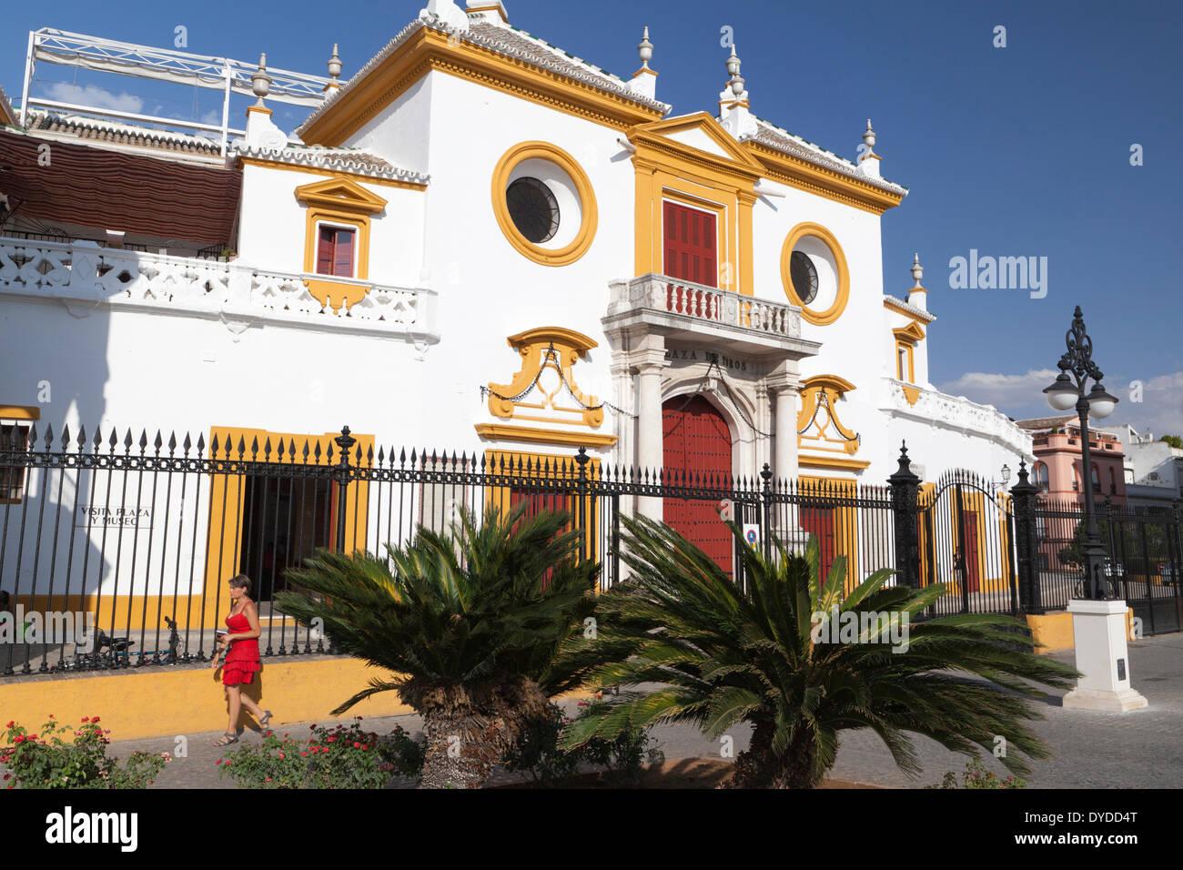 A woman dressed in red walks by the Plaza de toros de la Real Maestranza. - Stock Image