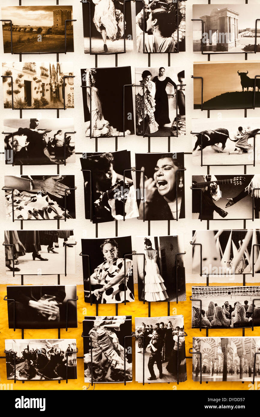 A wall rack of black and white postcards showing traditional Andalucian scenes. - Stock Image
