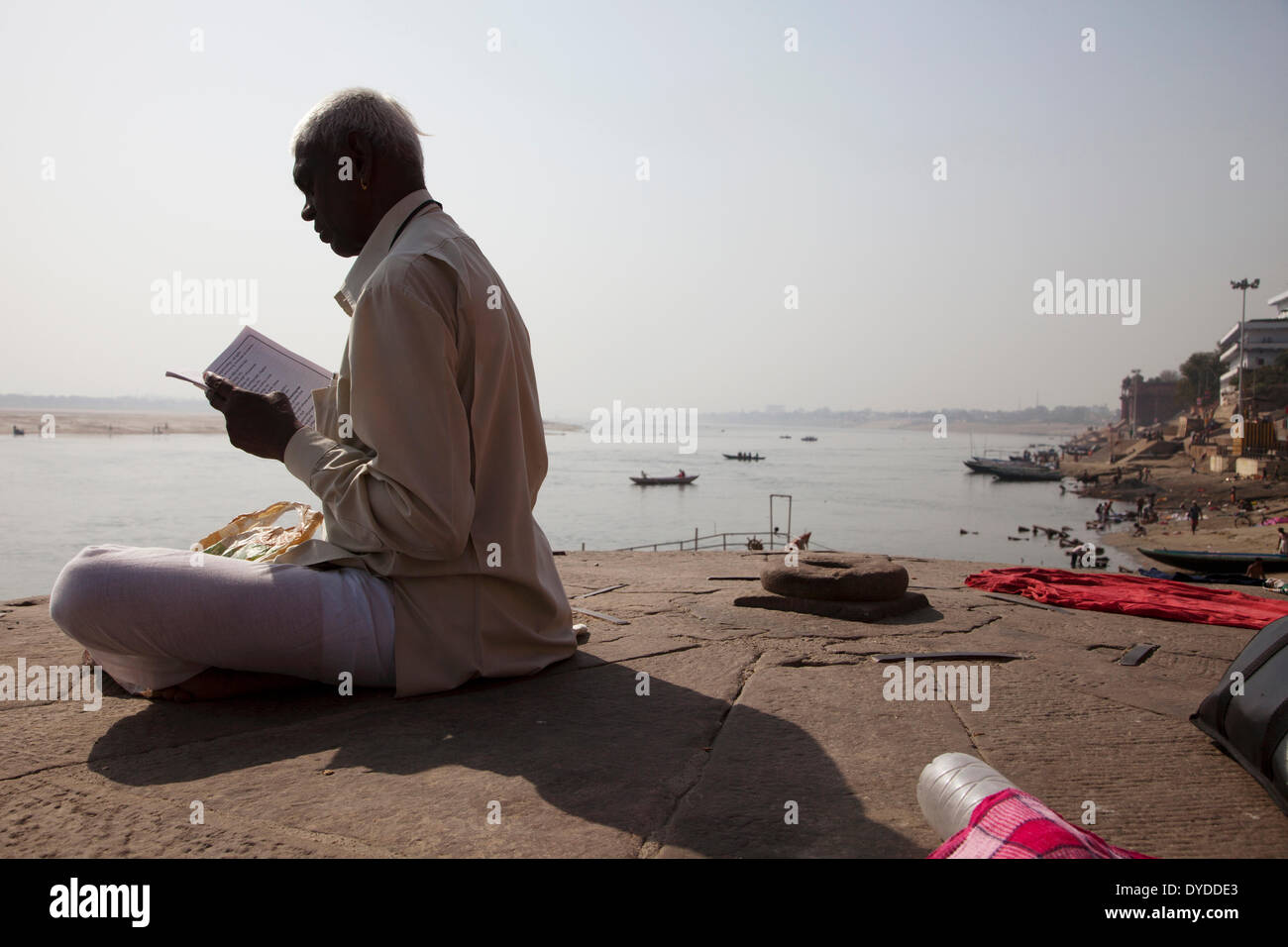 A man reading scriptures by the Ganges river. - Stock Image