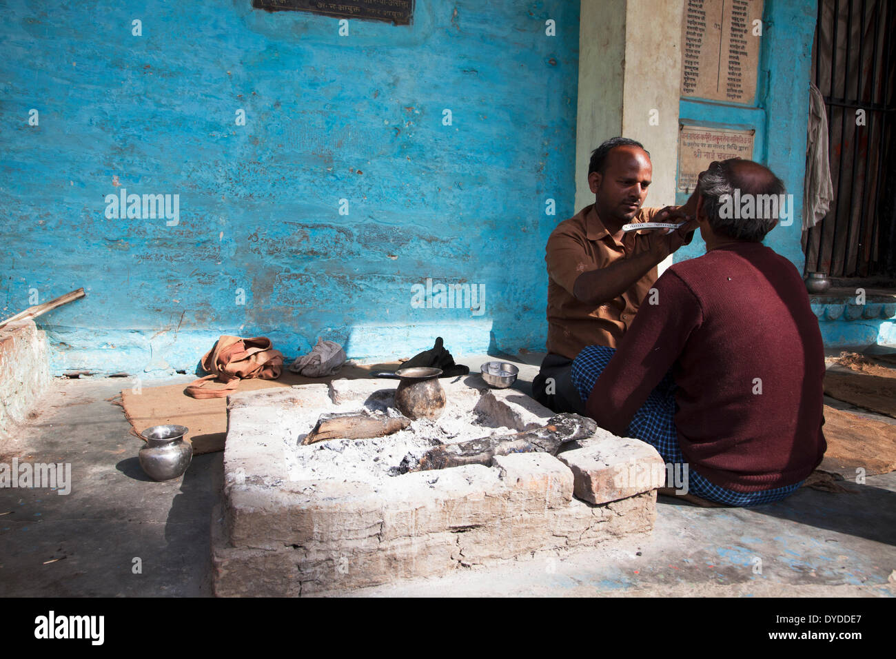 A barber at work on the ghats. - Stock Image
