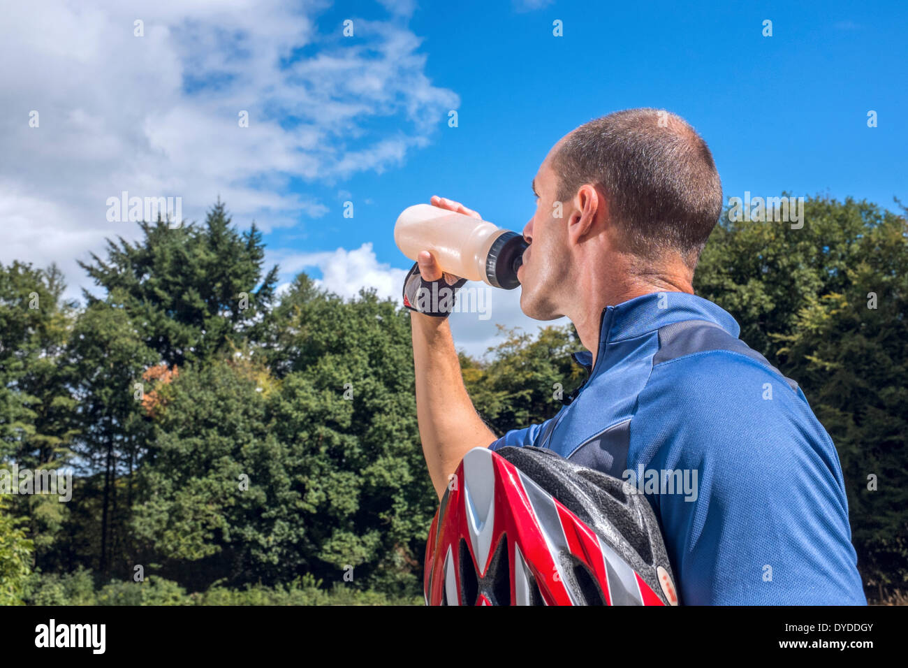 Male cyclist drinking from a water bottle. - Stock Image