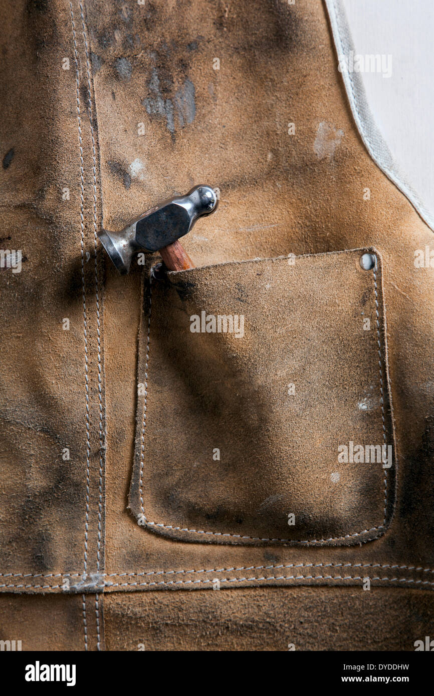 Leather workshop apron with a chasing hammer in the pocket. - Stock Image